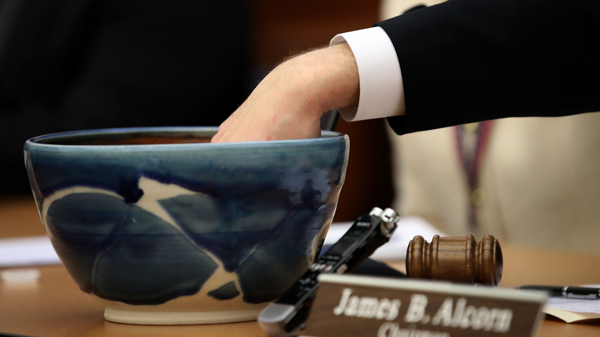 Someone has their hand in a bowl to draw names to settle an election tie