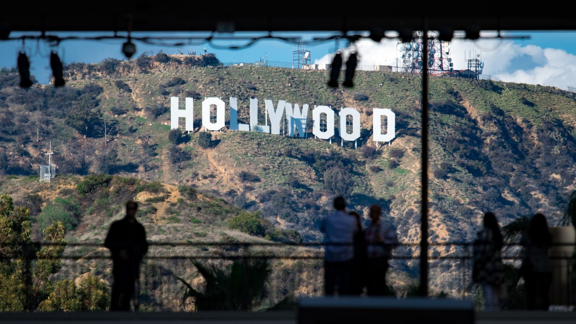 In this image, the Hollywood sign is visible in the background as a man stands and looks at it.