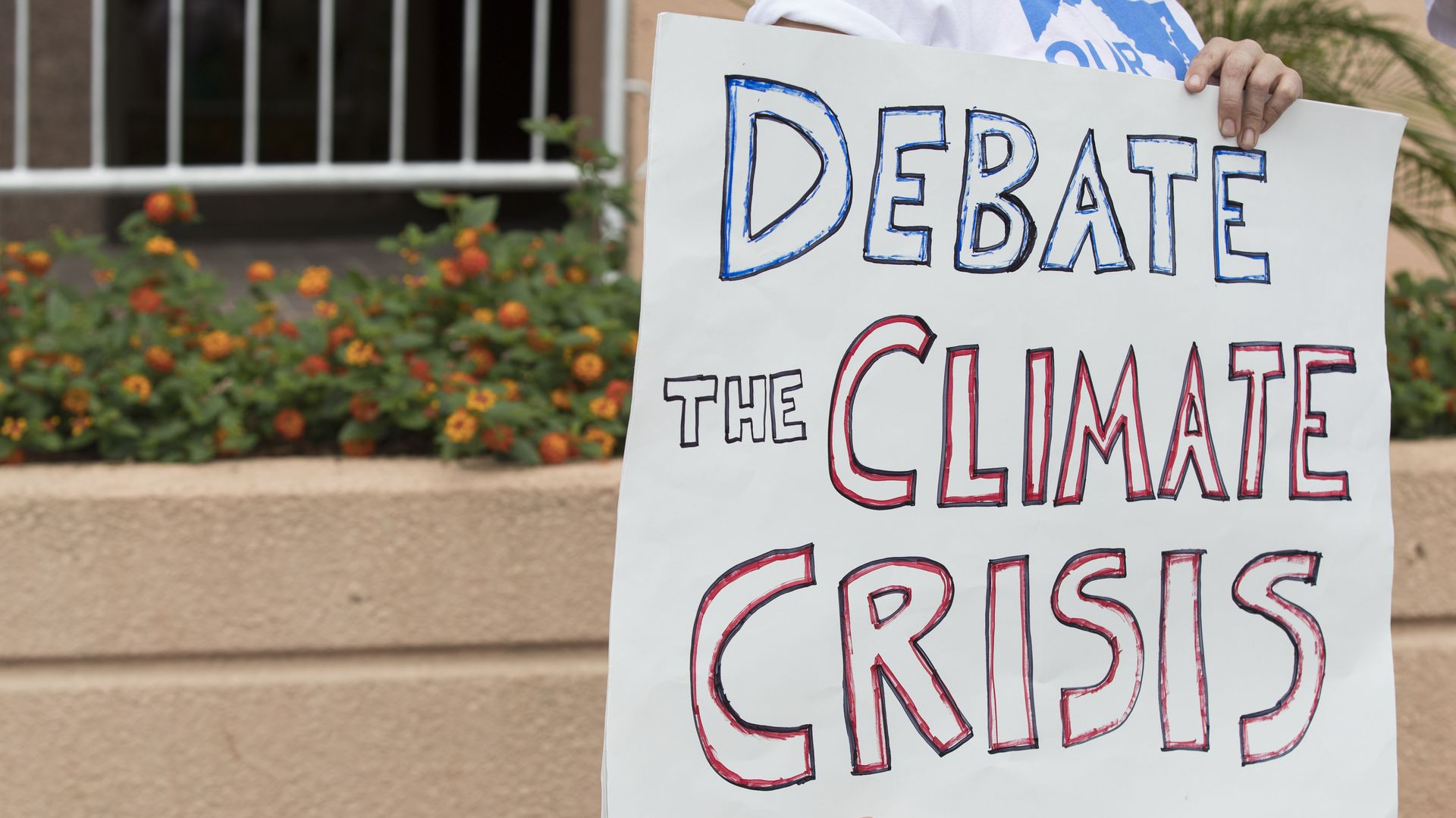 Photo of protestors wanting a climate specific debate outside the DC headquarters of the DNC