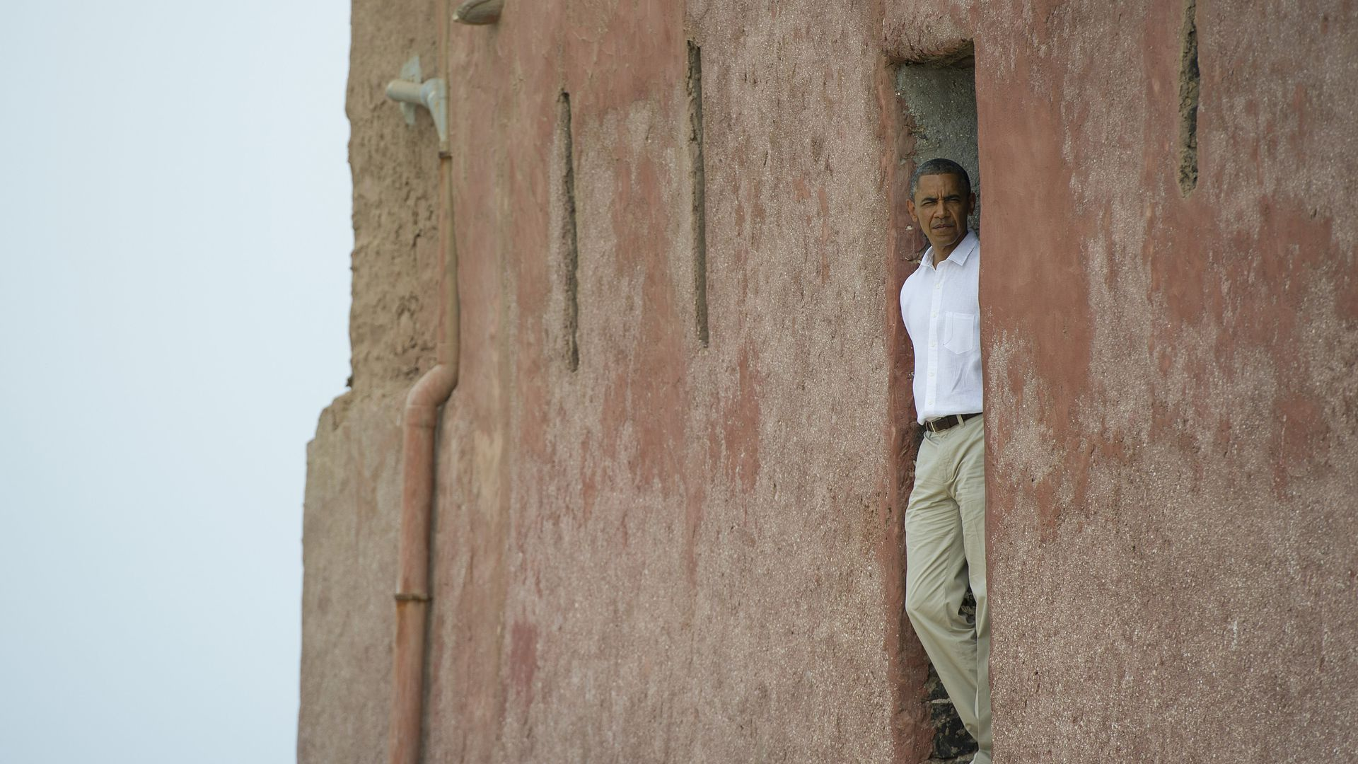 Obama stands in a doorway looking out