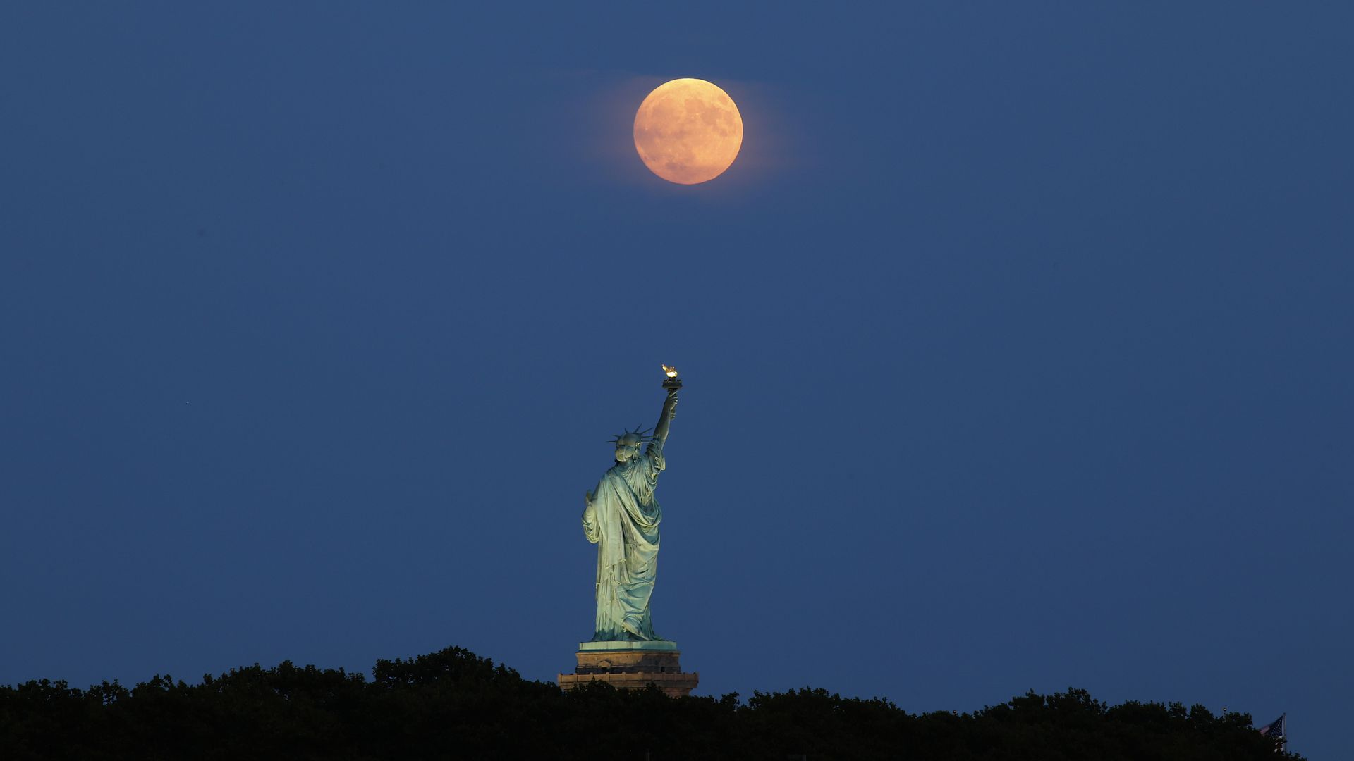 Statue of Liberty on dark background with orange moon