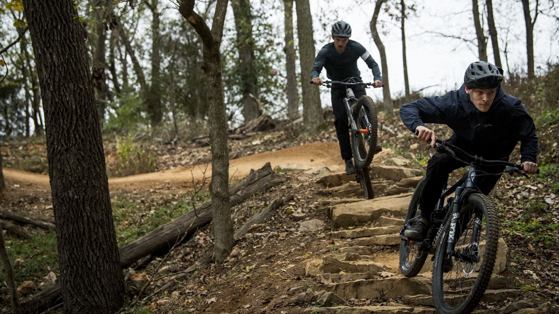 Two cyclists ride bikes on a dirt path