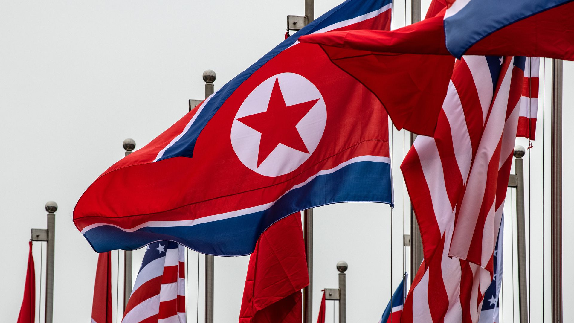 In this image, North Korean and US flags wave over each other