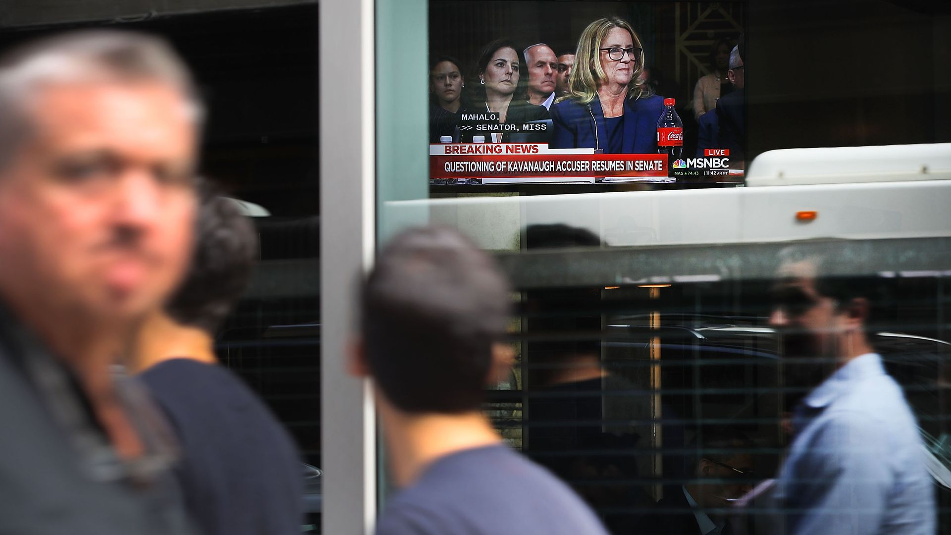 People walk by as the Ford hearing plays on a TV inside a window.