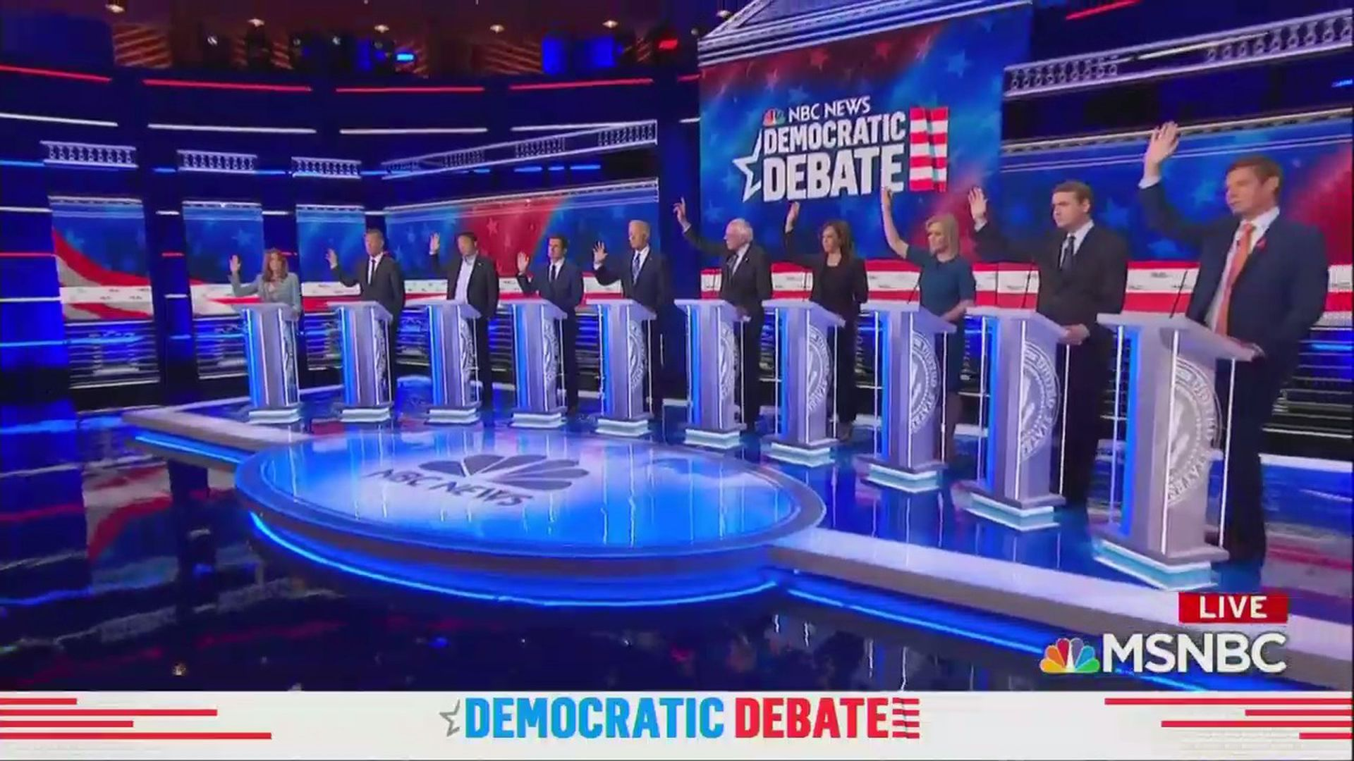 2020 Democratic candidates raise their hands on the debate stage supporting healthcare for undocumented migrants