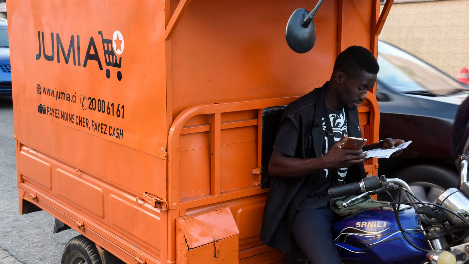 A man studies a piece of paper while leaning against an orange Jumia delivery vehicle
