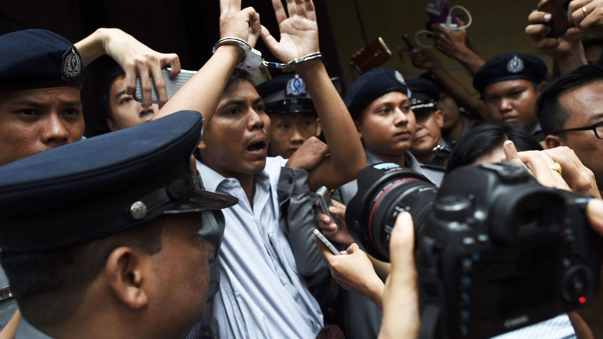 Reuters journalist Kyaw Soe Oo gets escorted by police after being sentenced to seven years in prison