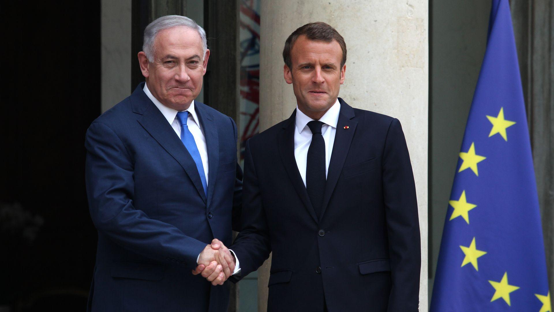 Israeli prime minister Benjamin Netanyahu shakes hands with French president Emmanuel Macron