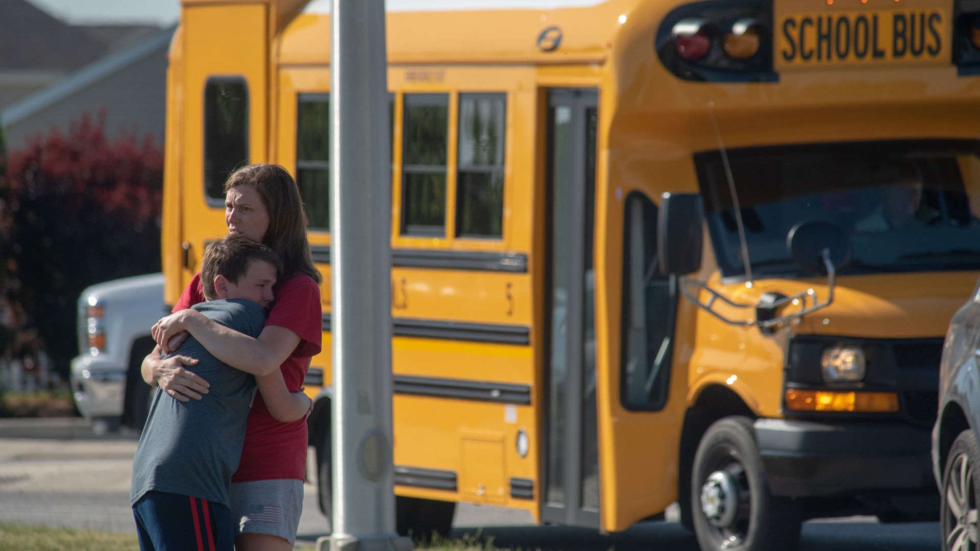 A woman and young boy hug near a school bus.