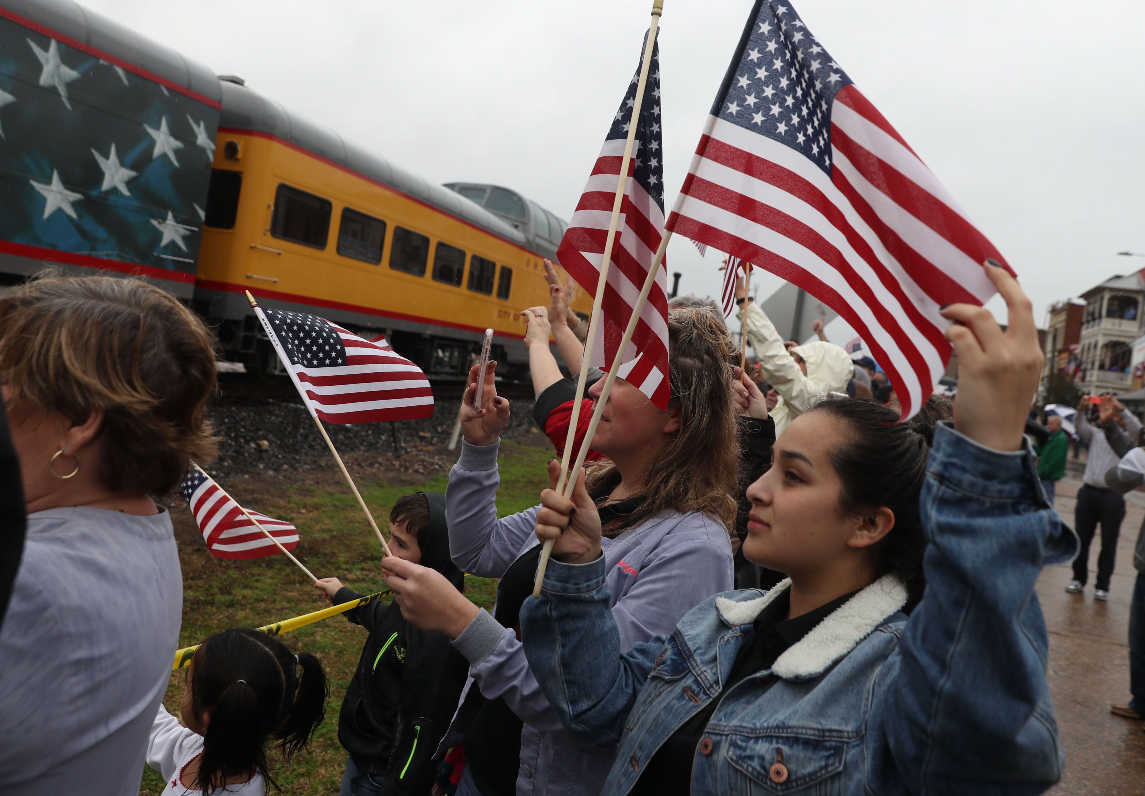 People waving along George H.W. Bush's remains via train in Texas