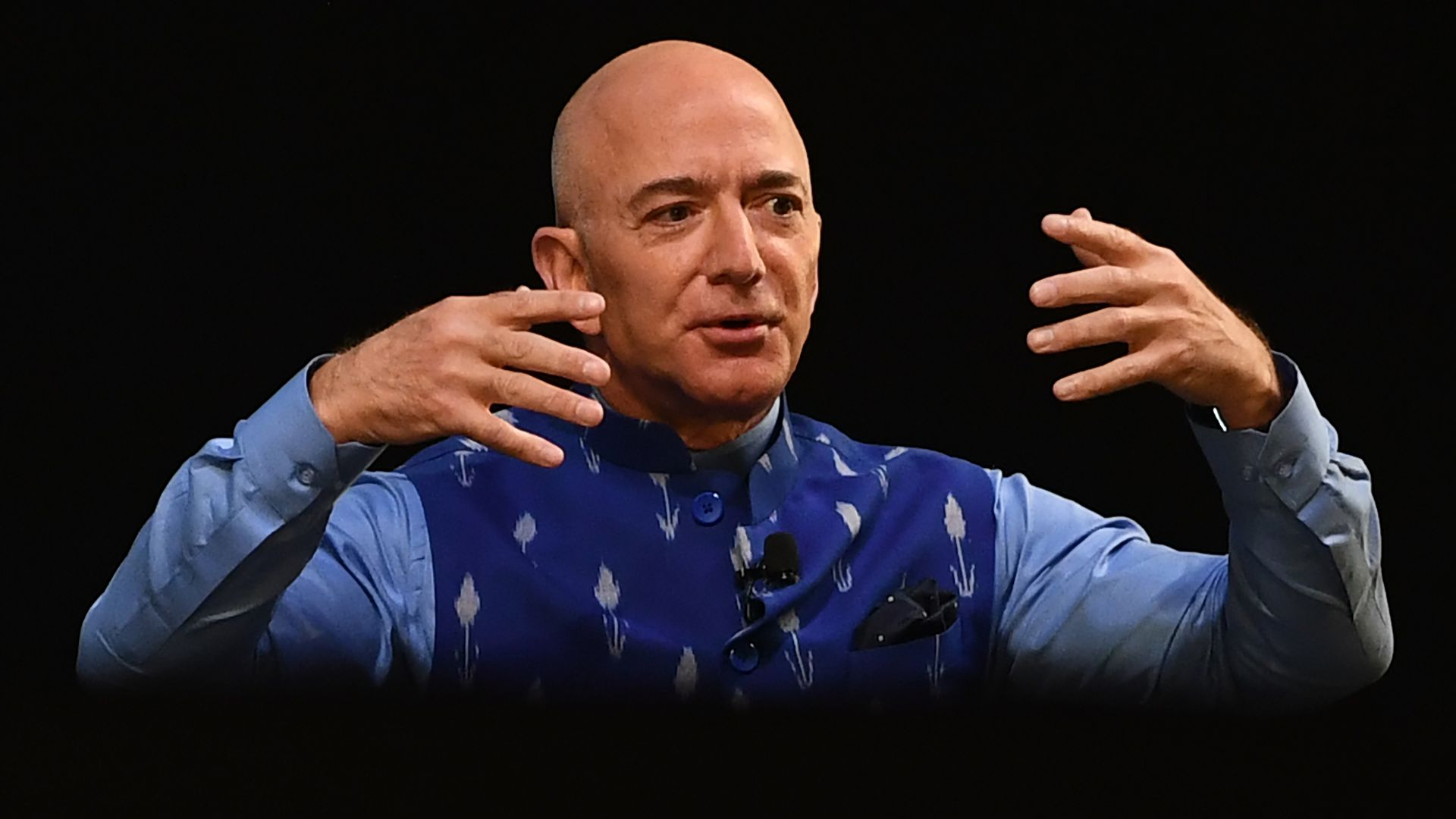 In this image, Bezos sits on stage with his hands in front of his face