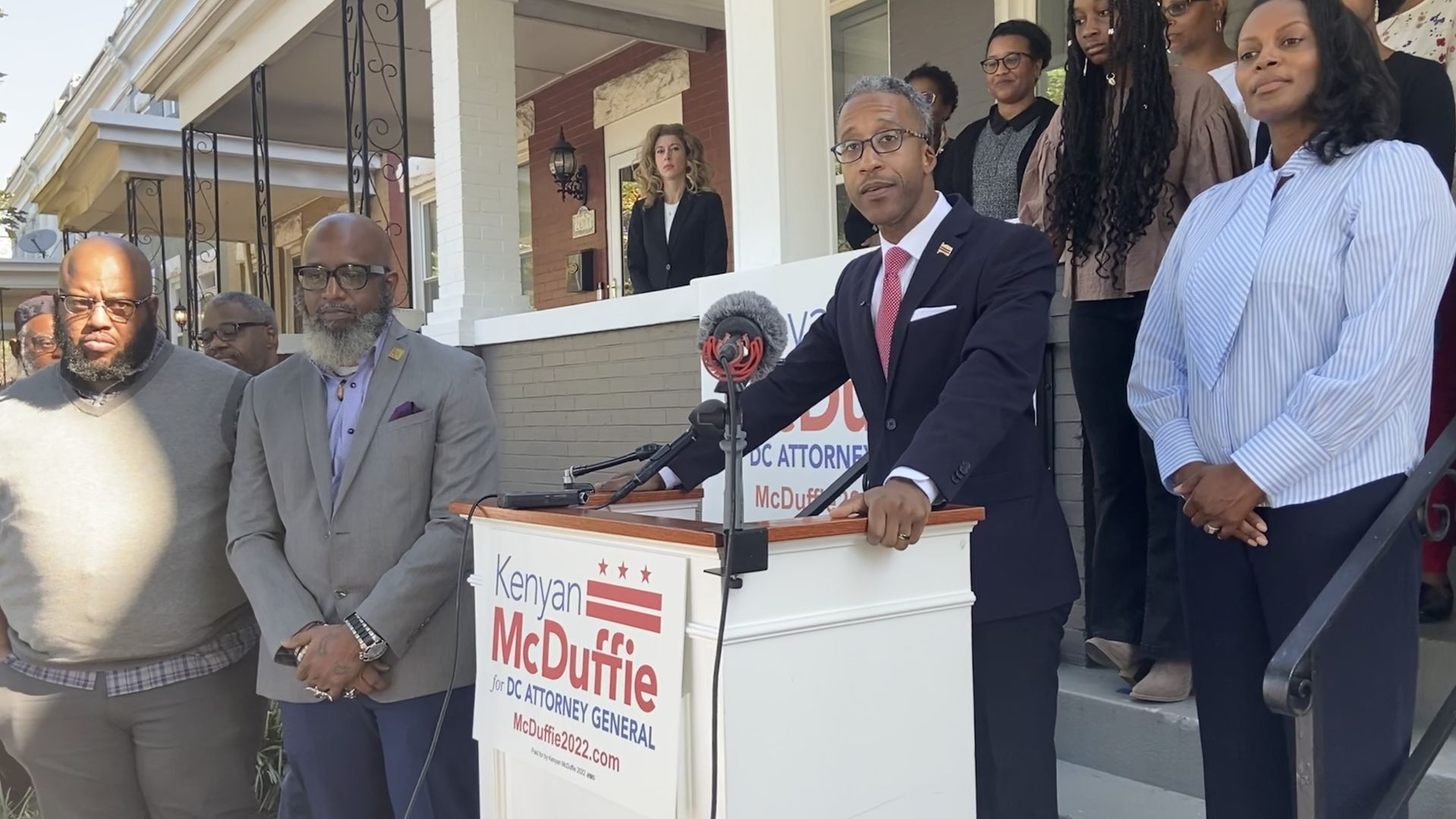 Council member Kenyan McDuffie speaks before a podium surrounded by family and friends.