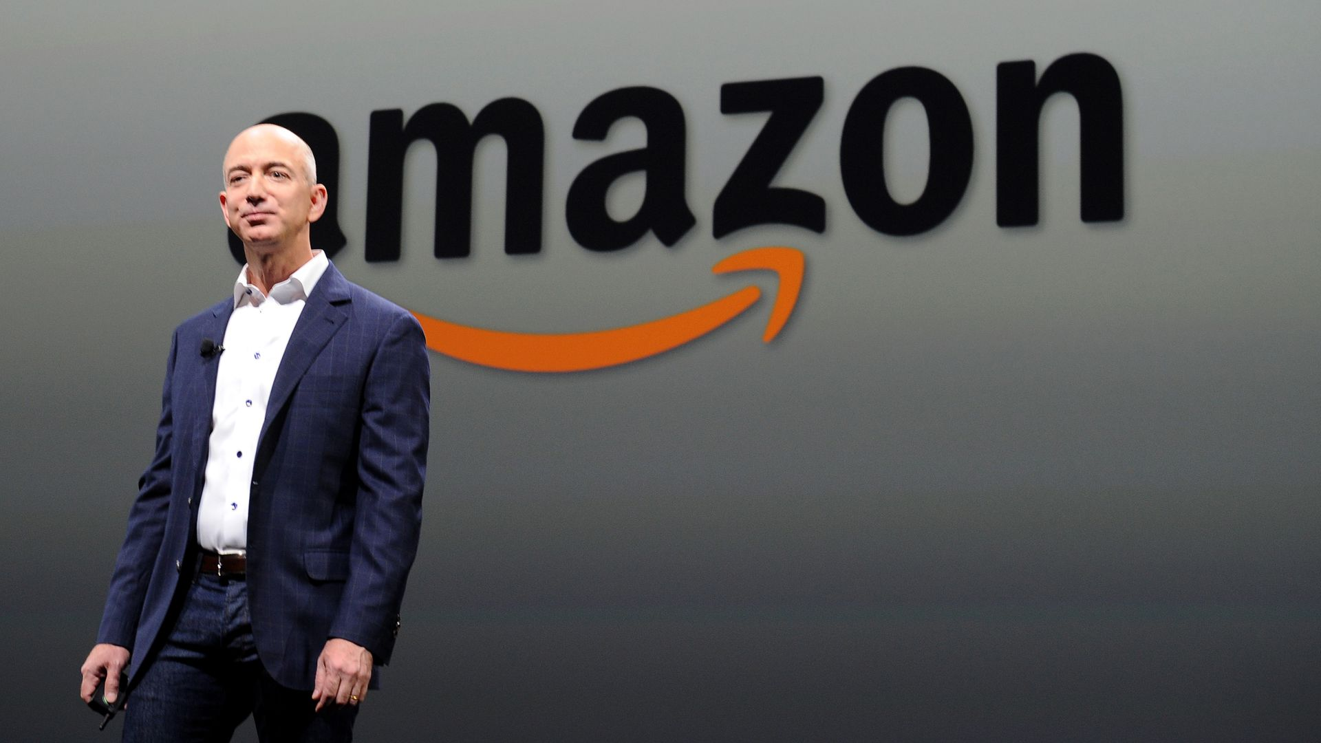 Amazon CEO Jeff Bezos stands in front of the Amazon logo on stage.