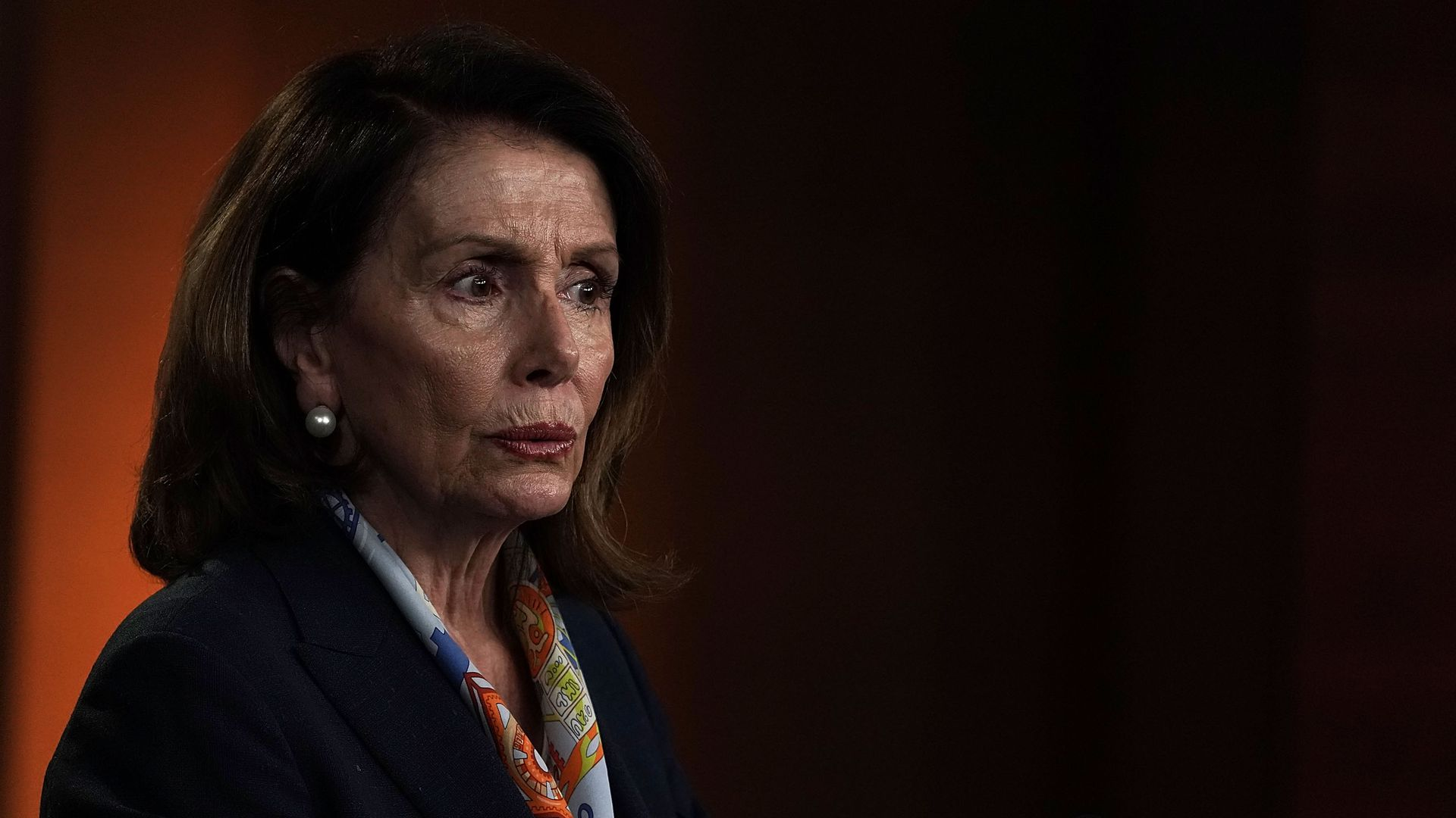 Nancy Pelosi in a dark suit with a colorful scarf before a black and orange backdrop.