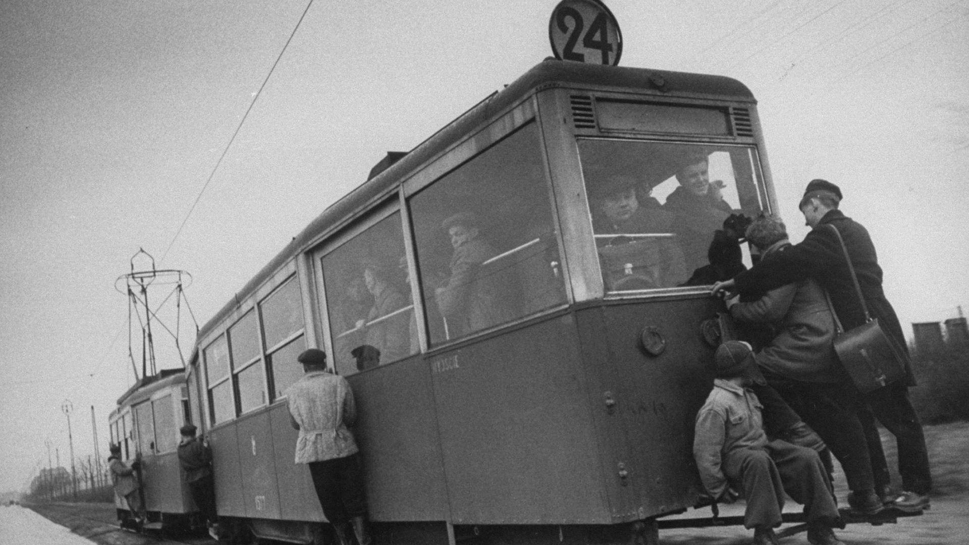 People hanging off a streetcar.