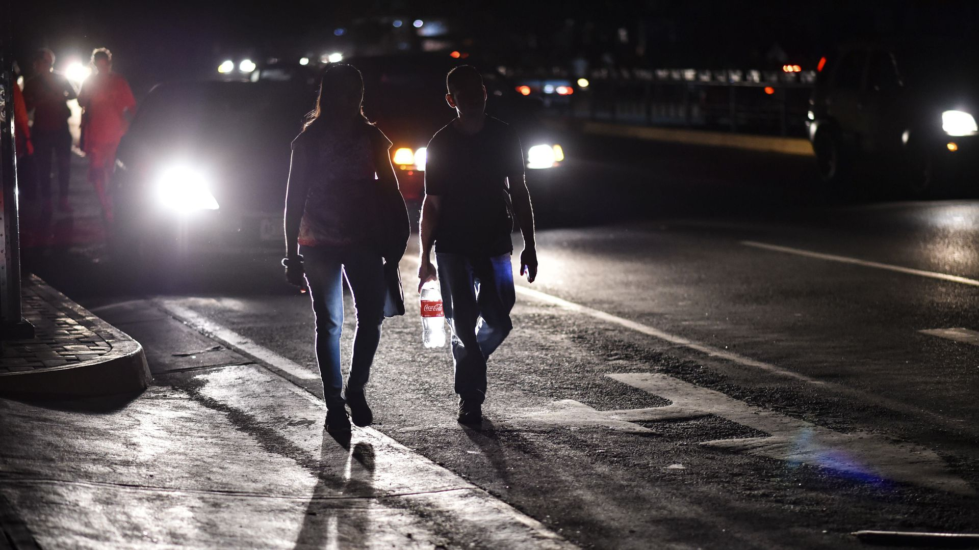 Two Venezuelan pedestrians walk down a dark street.