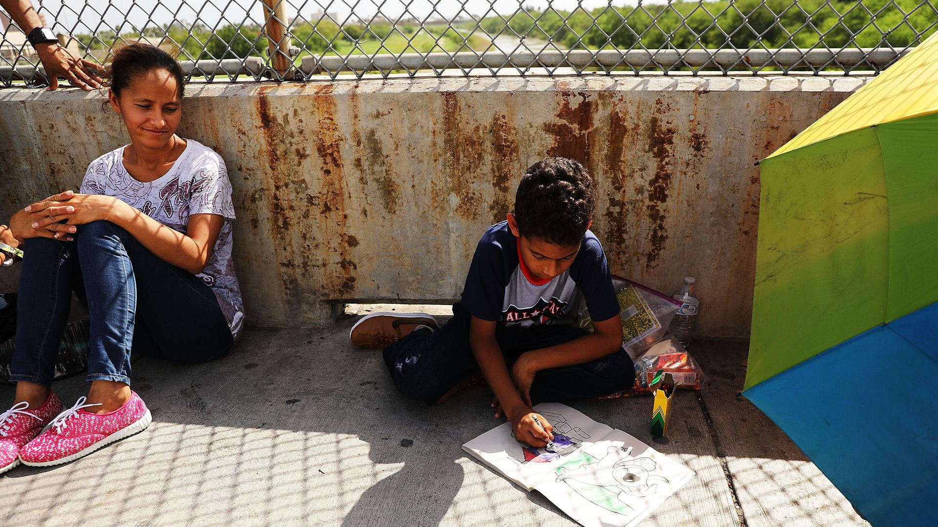 A migrant child coloring along the US-Mexico border