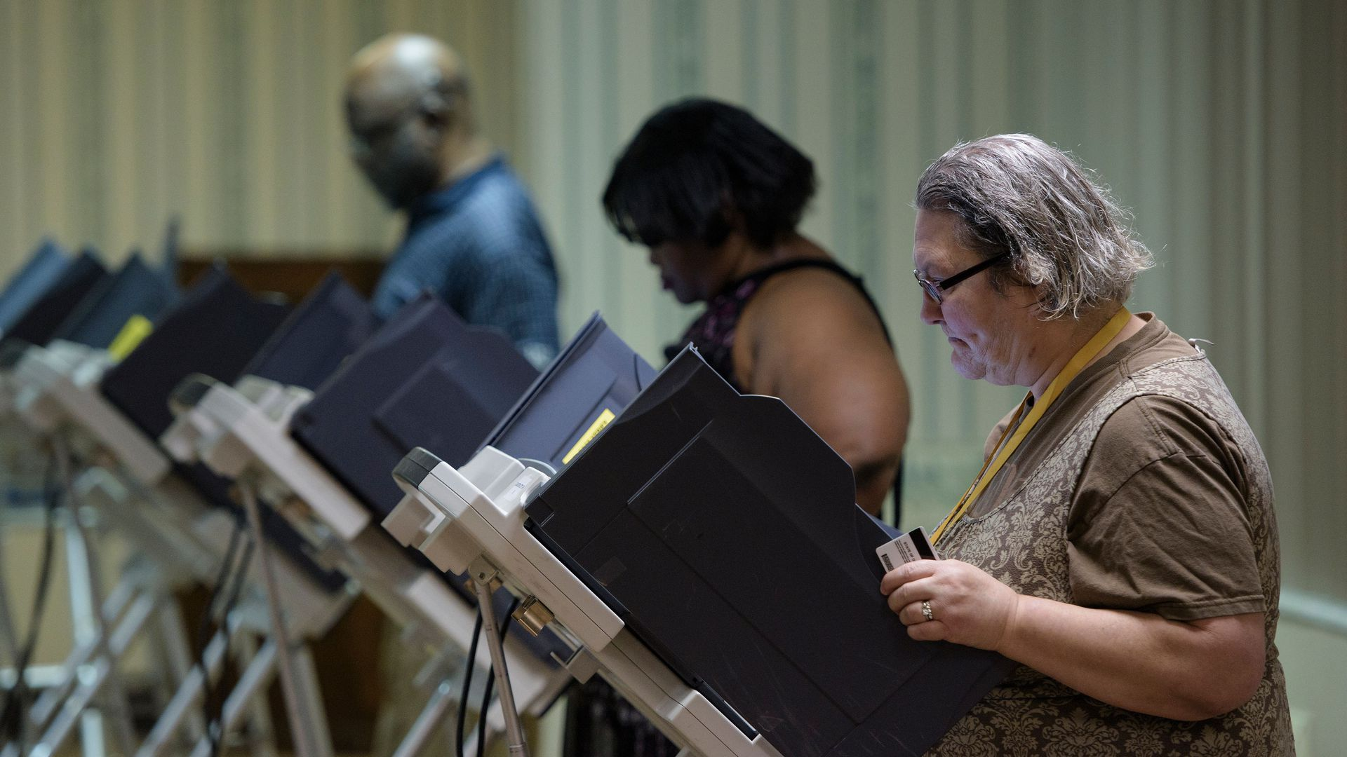Three voters voting on electronic machines in a row.