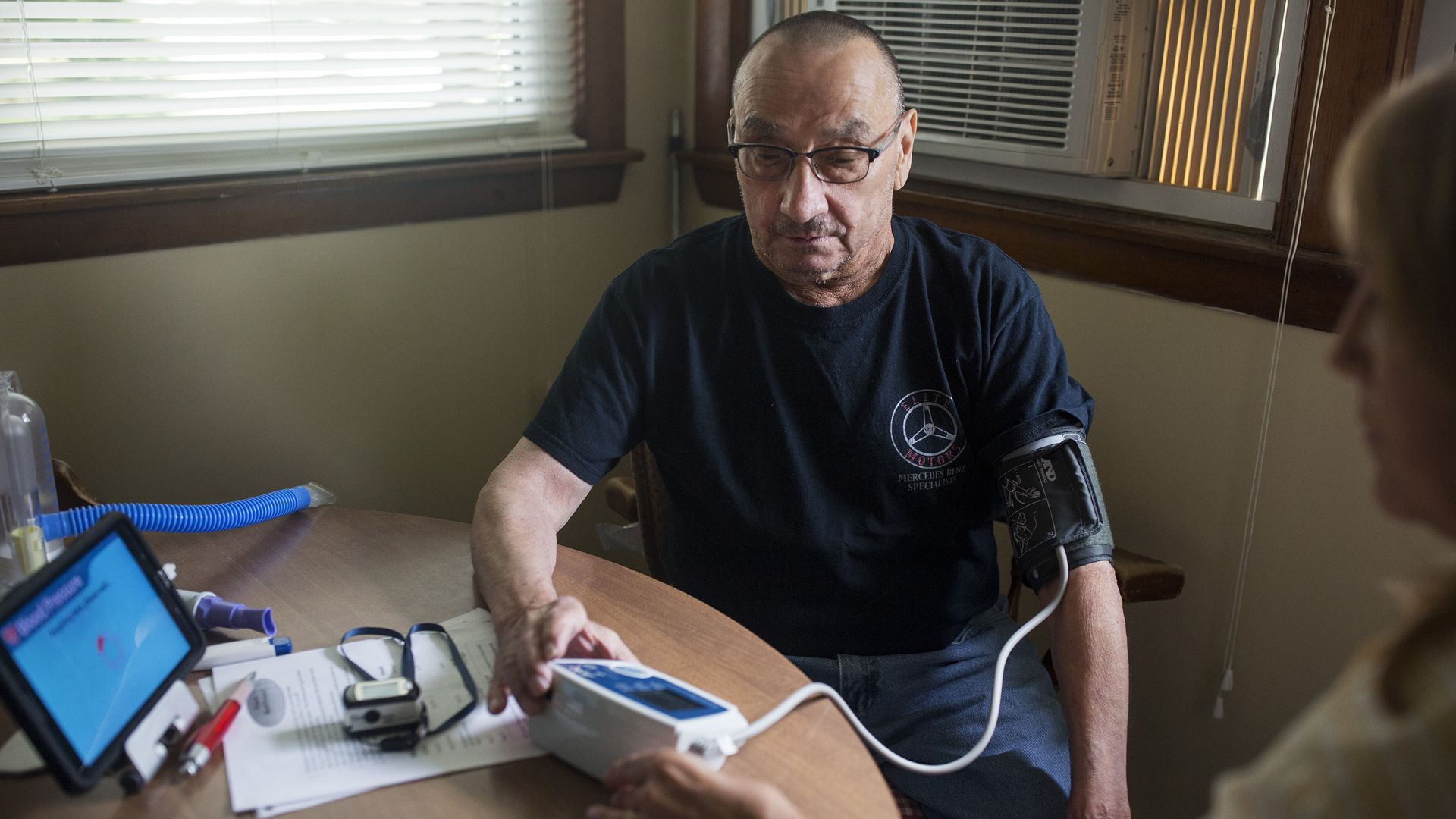 A man measures his vitals and sends the data electronically to nurses.