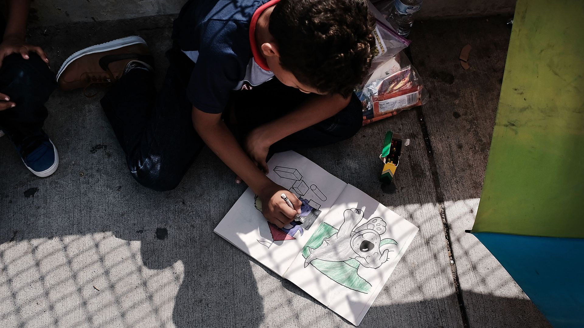 A migrant child colors at the border