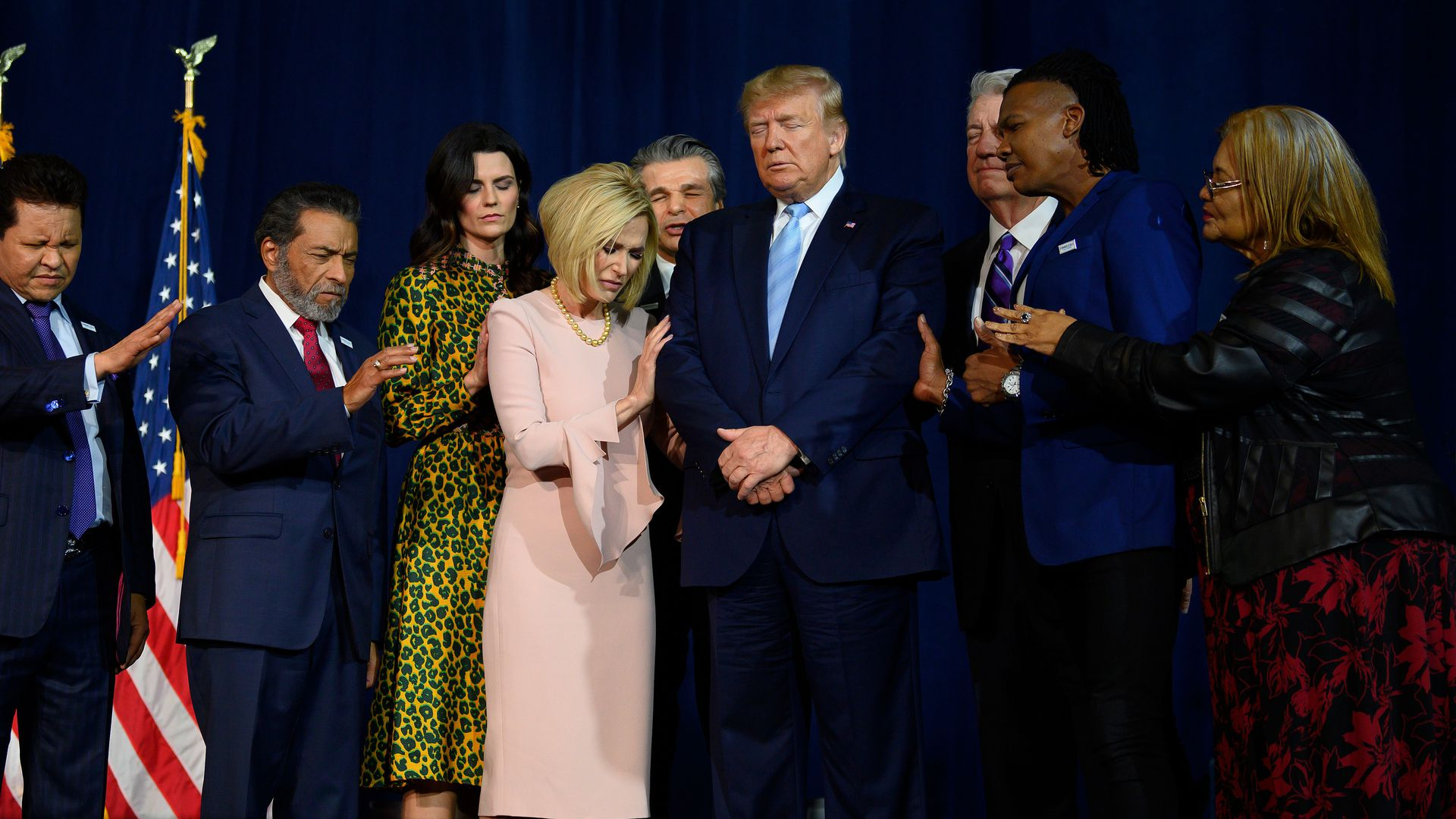 President Trump stands in a prayer circle with faith leaders