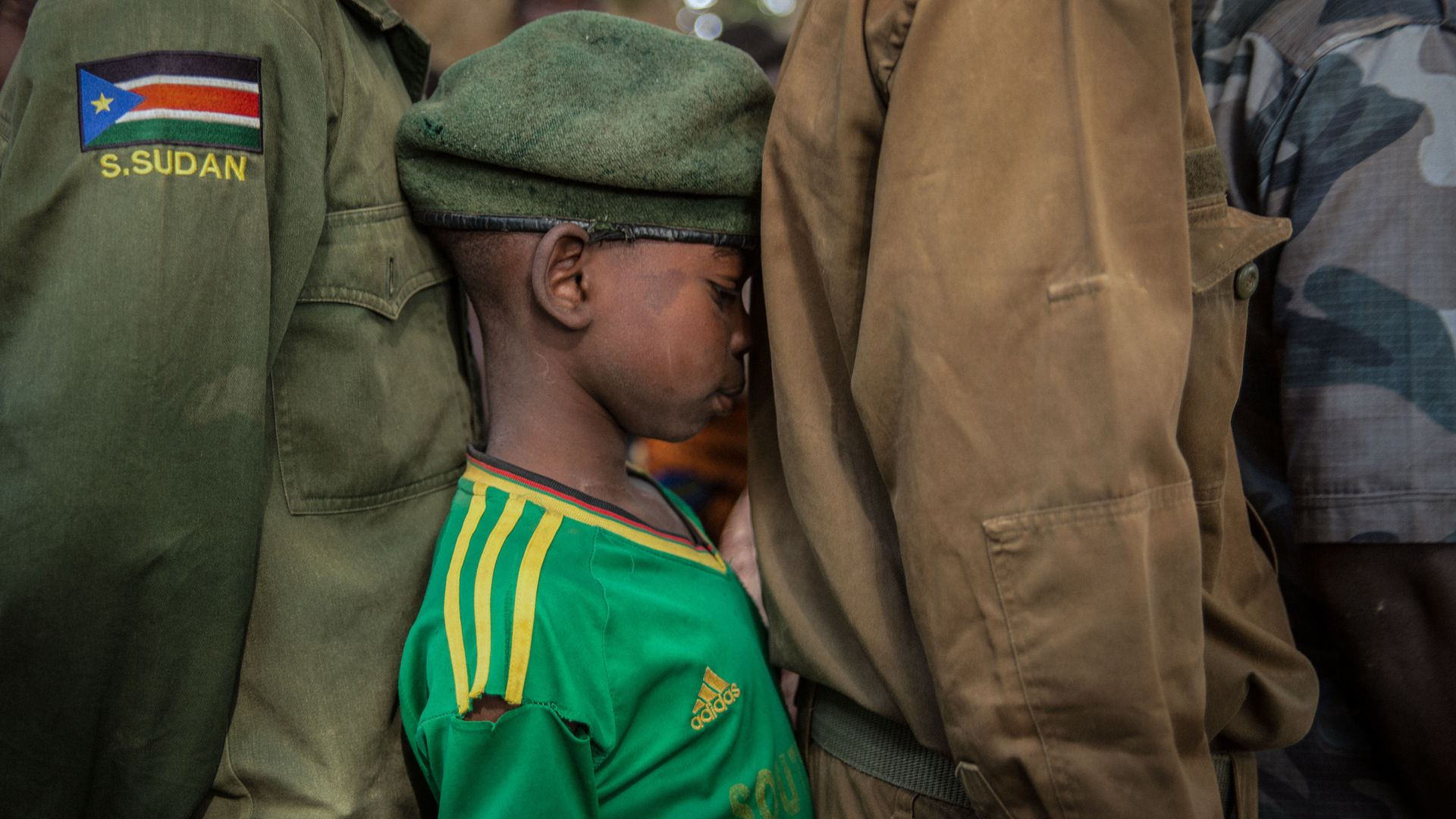 Newly released child soldiers wait in a line for their registration