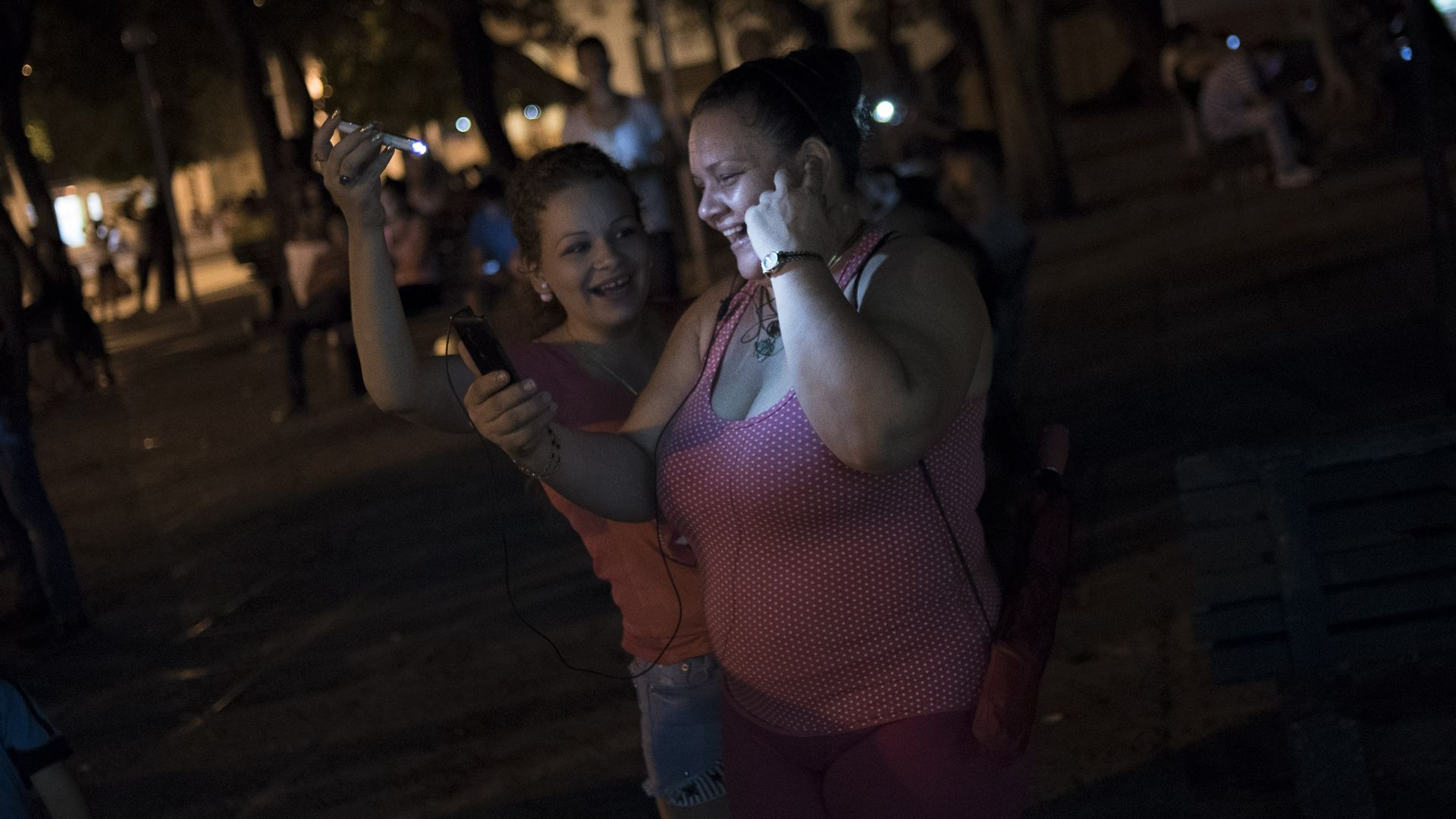A Cuban woman uses her mobile phones to connect to the internet and speak with her relatives abroad