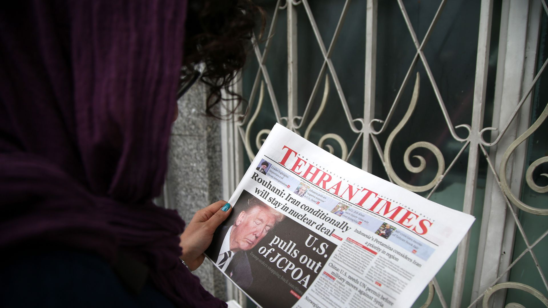 A woman reads Tehran Times on May 9, 2018 in Tehran, Iran. US President Donald Trump announced 'withdrawal' from Iran nuclear deal on May 9, 2018.