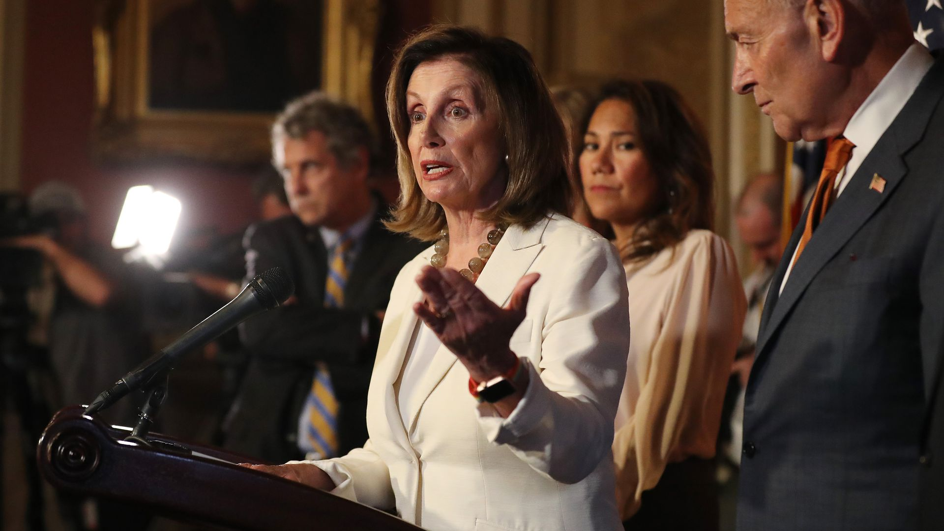 Nancy Pelosi gestures at a press conference