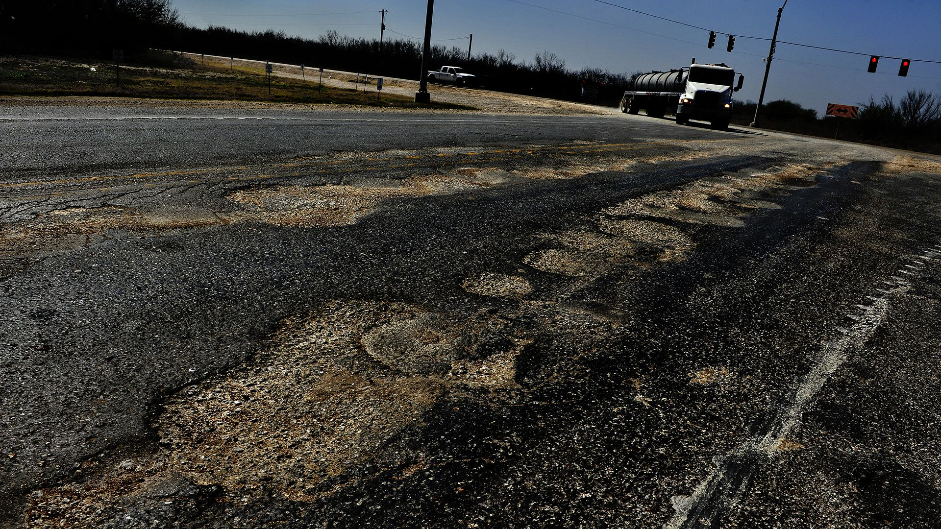 Sections of Highway 72 near Fowlerton, Texas, show the wear and tear from the huge amount of oil industry truck traffic.