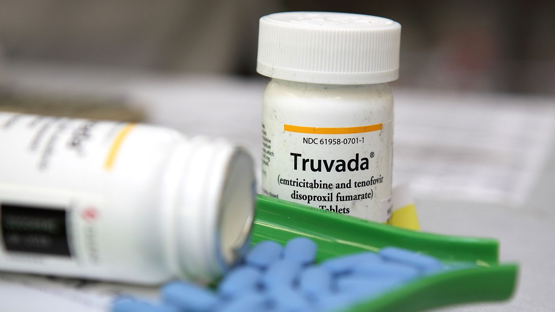 In this image, blue Truvada pills are being counted at a pharmacy. A pill bottle sits behind the counter.