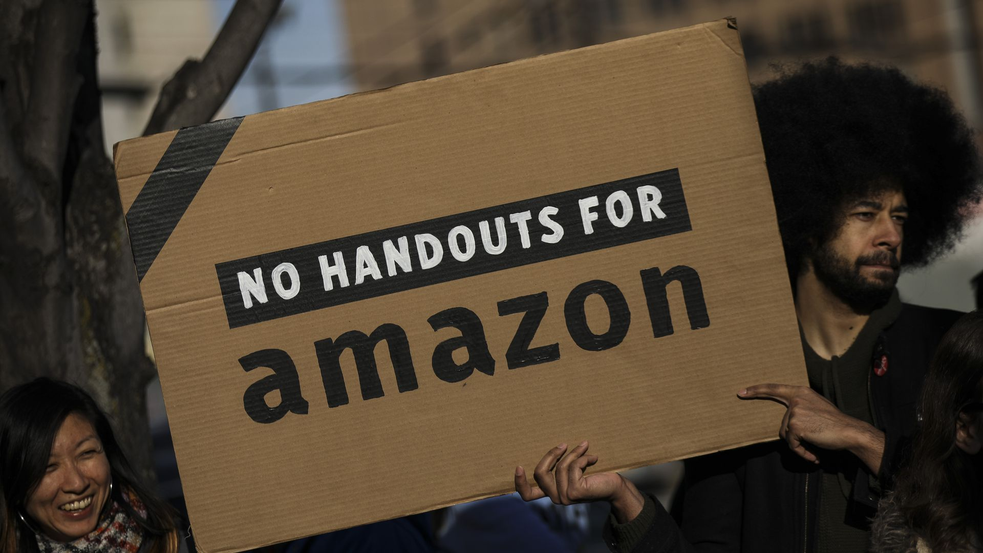 Protestor carries a sign saying no handouts for amazon