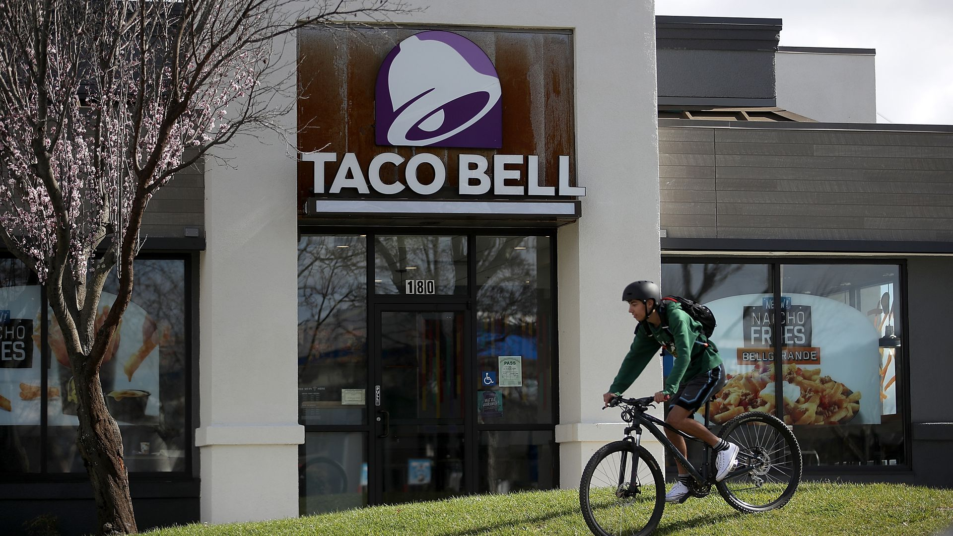 A customer rides his bike in front of Taco Bell.