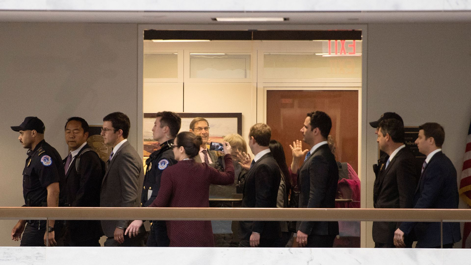 Staffers wave through a glass door at Mark Zuckerberg as he walks by