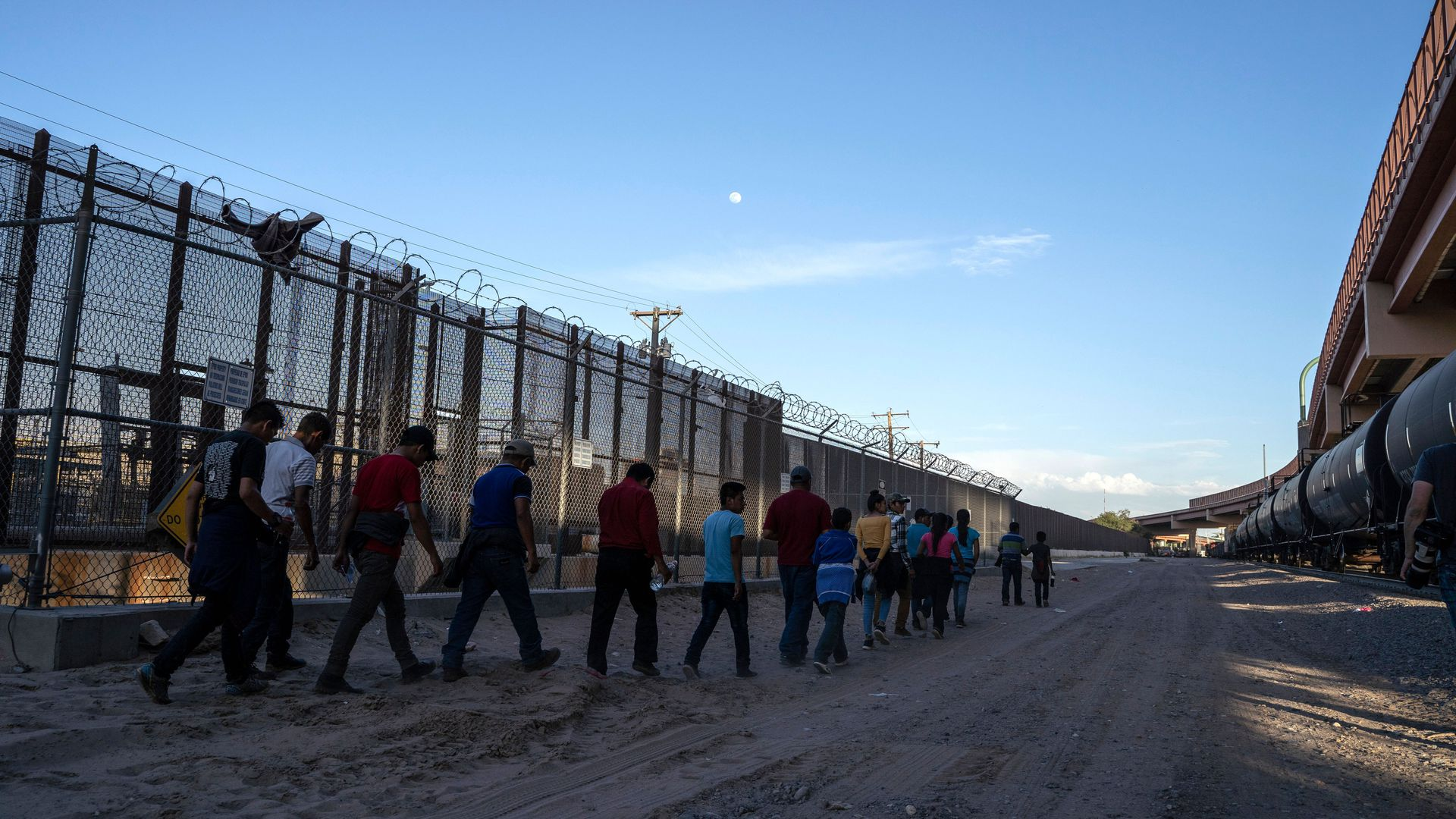 In this image, a line of migrants walk outside near a tall chain link fence.
