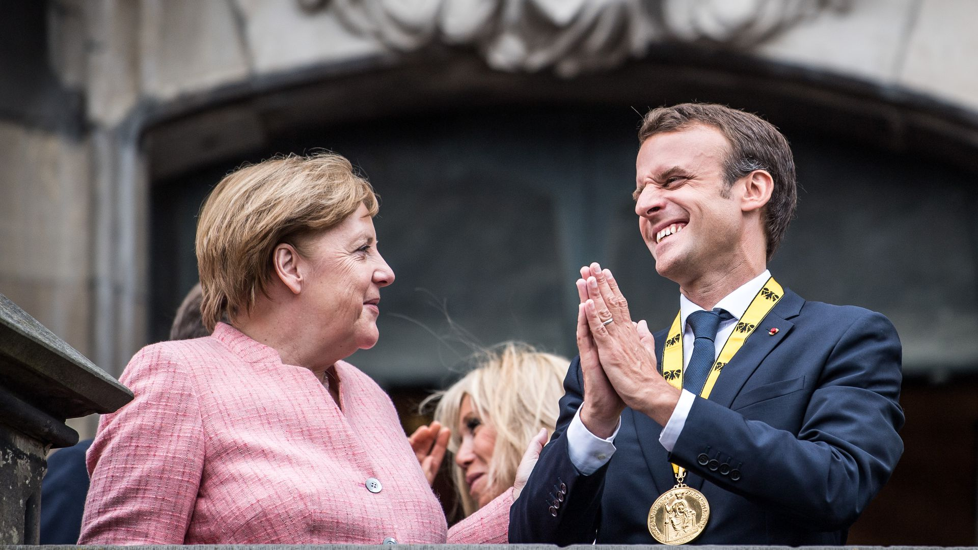 German Chancellor Angela Merkel and French President Emmanuel Macron gesture on the balcony of the town hall of Aachen