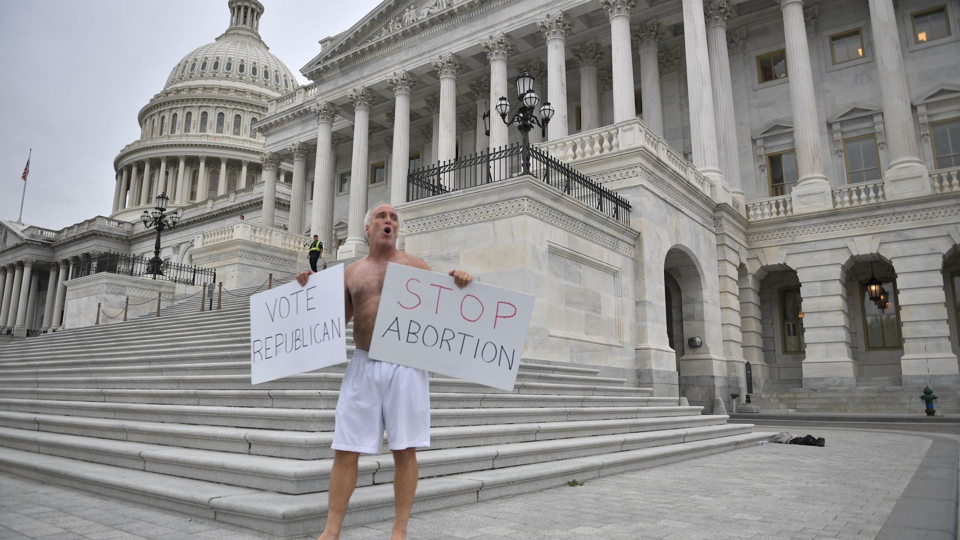 MAn protesting in front of the U.S. capitol saying stop abortion vote republican