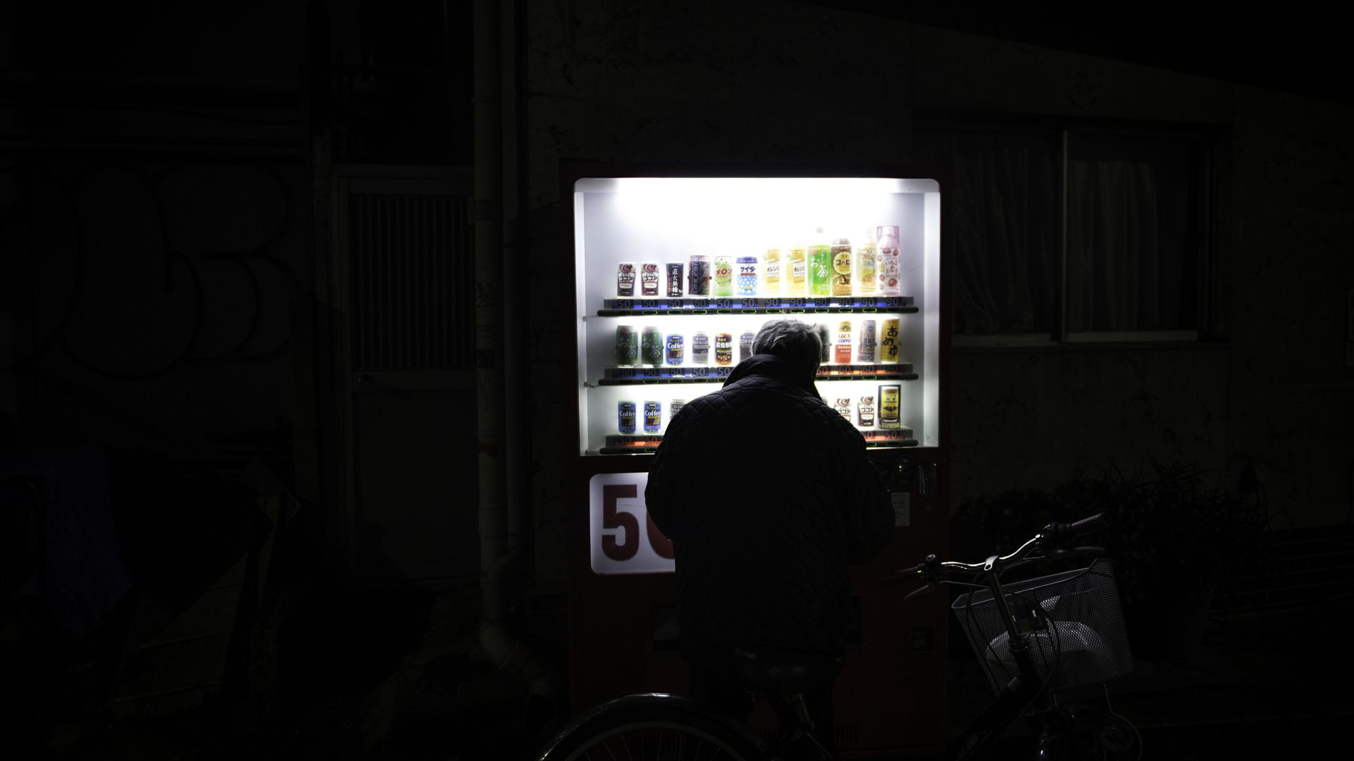 A man silhouetted in front of a vending machine.