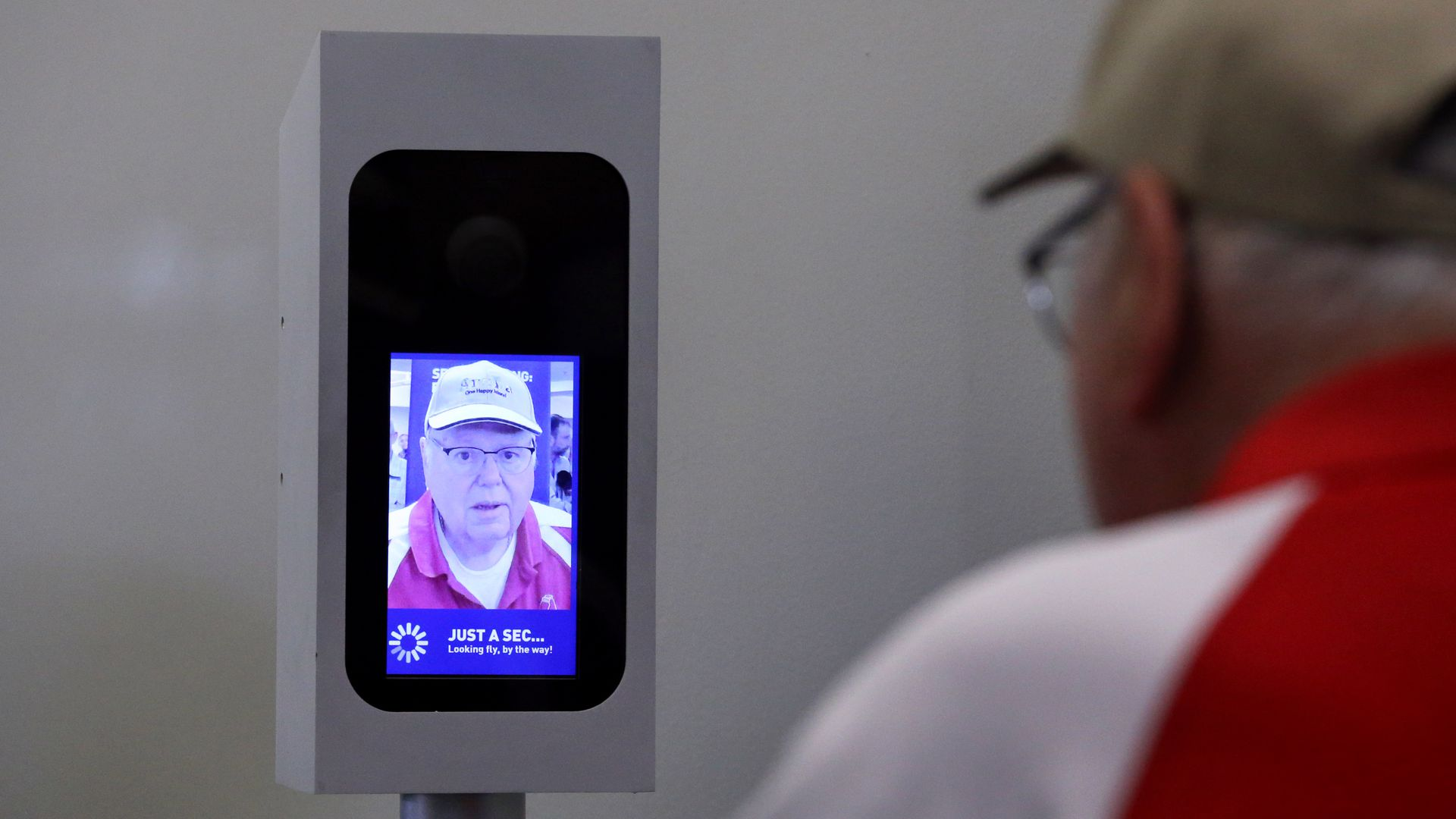 A man uses a facial-recognition system camera to board a JetBlue flight.