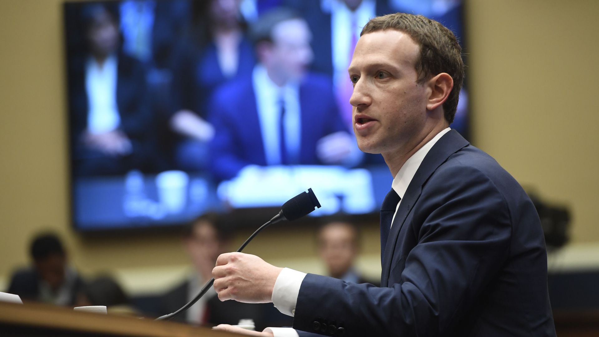 Mark Zuckerberg testifying in front of a big-screen TV that also shows him testifying