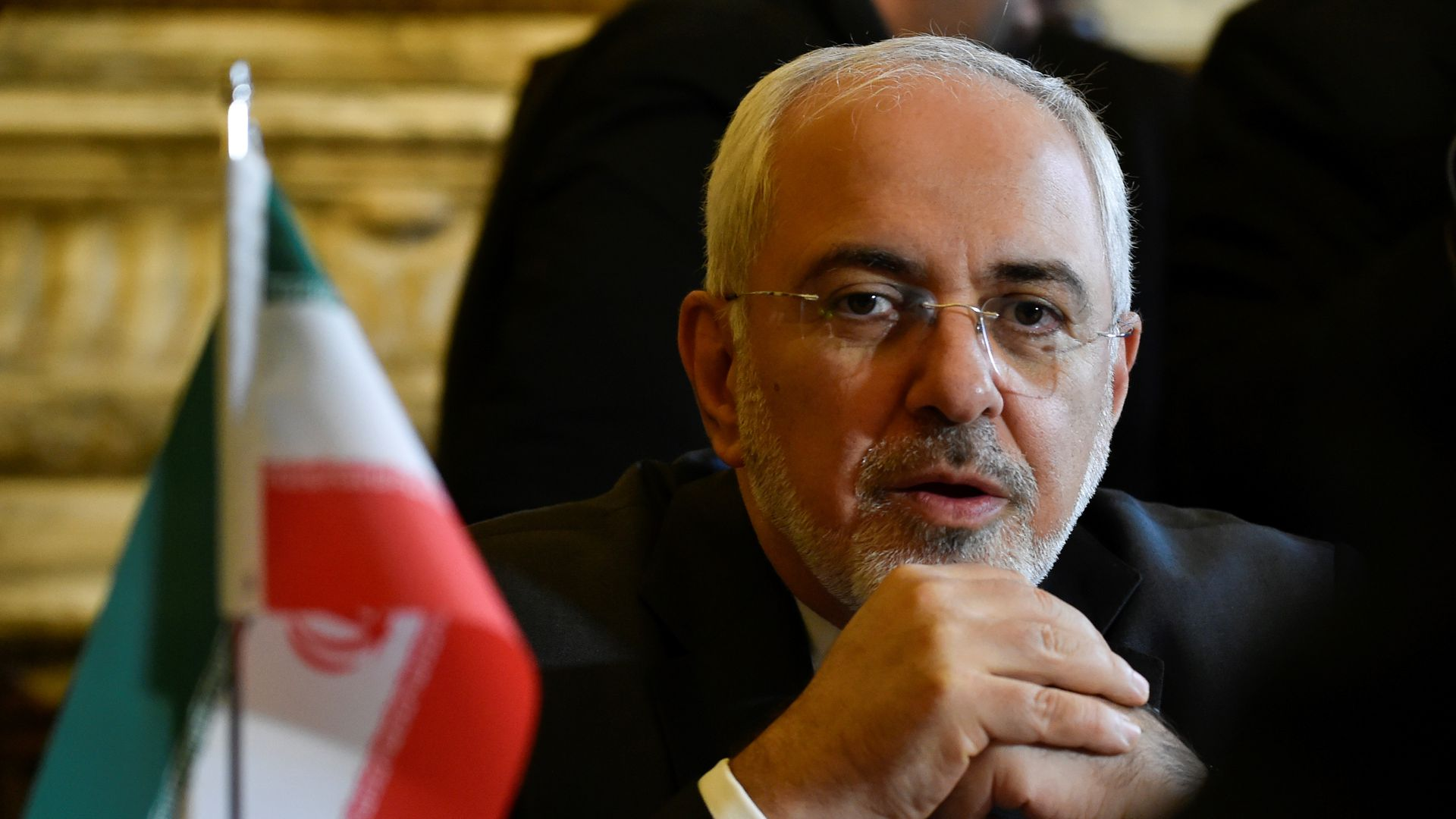 Zarif sits next to an Iranian flag