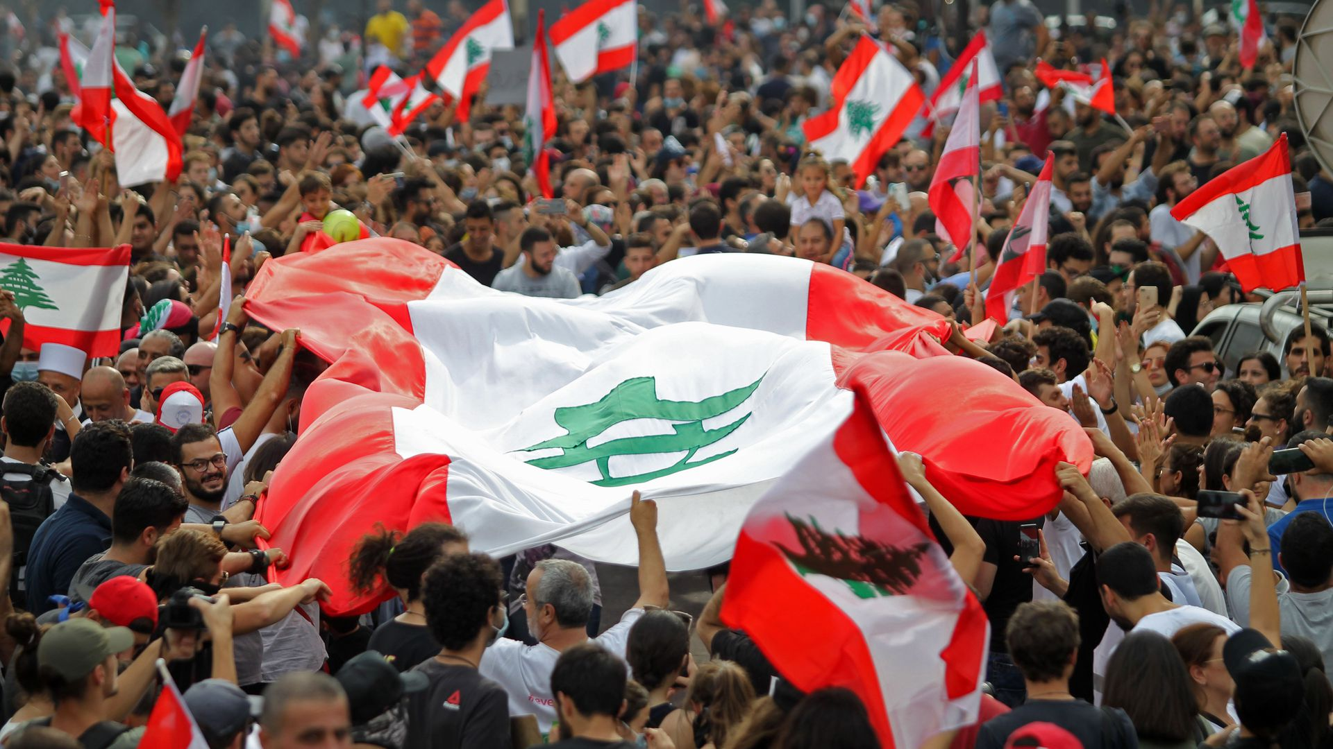 Lebanese protesters with a large Lebanese flag