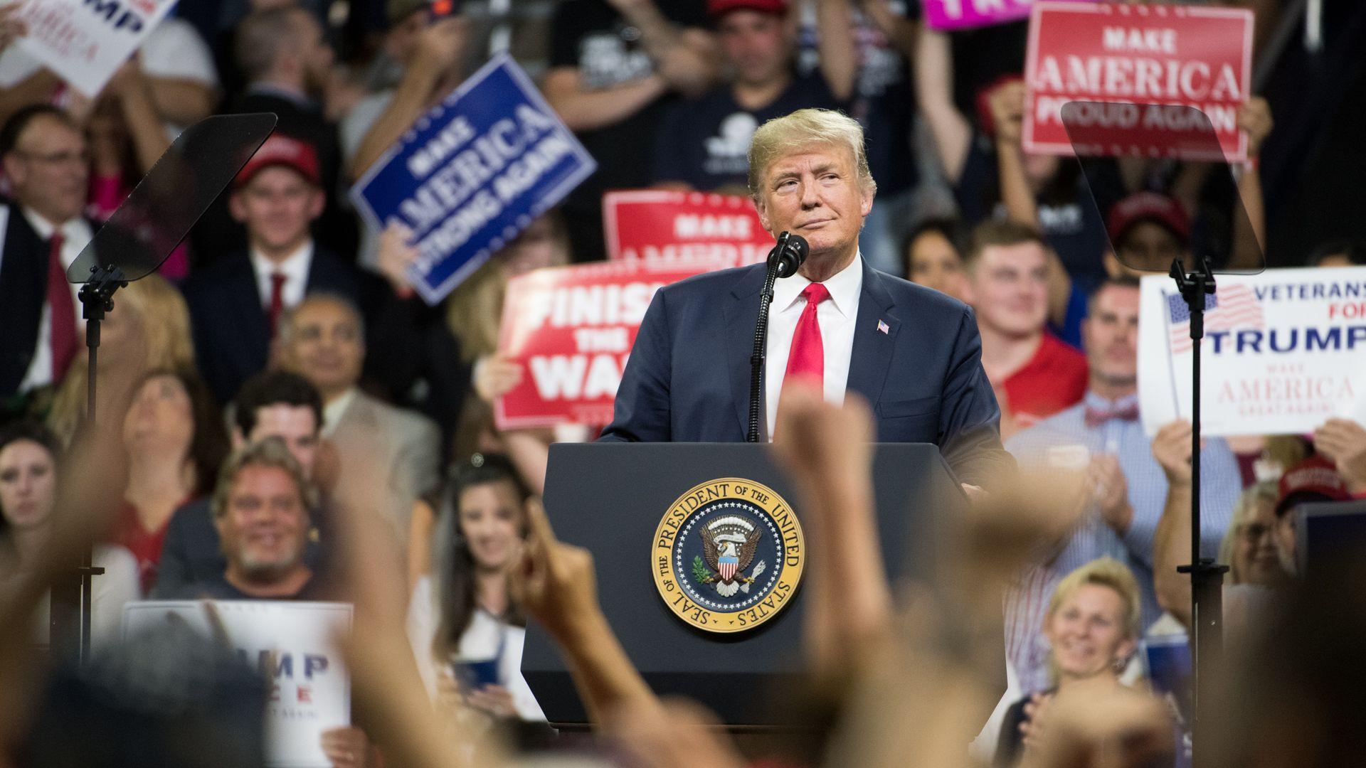Donald Trump at a rally, smiling.