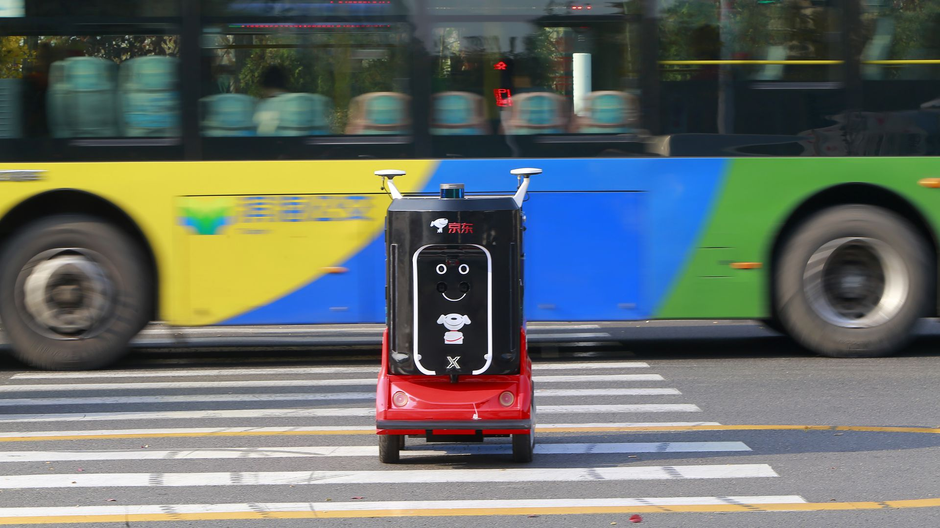 A red and black robot with a smiley face rolls across the street