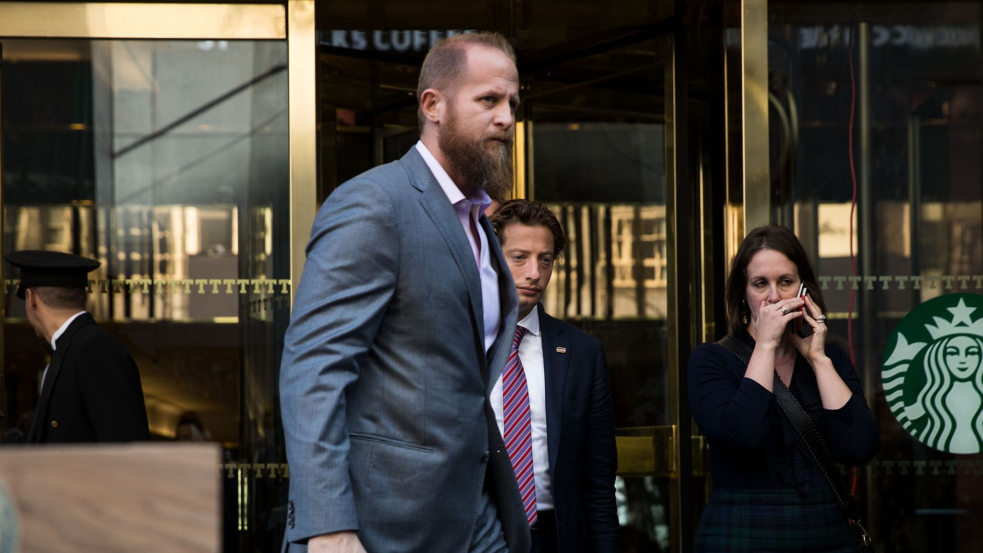 Brad Parscale walking in front of a Starbucks in a grey suit