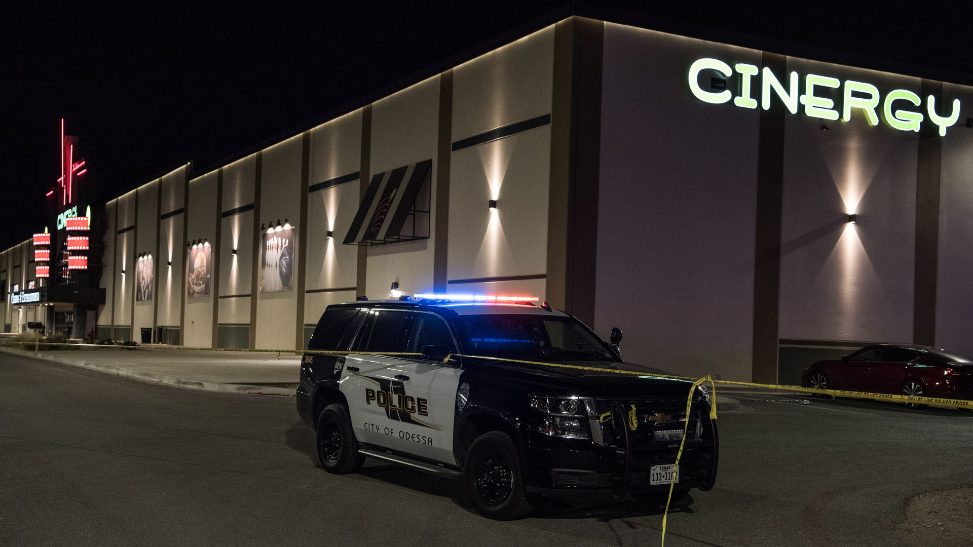 Police cars and tape block off a crime scene nearby to where a gunman was shot and killed at Cinergy Odessa movie theater