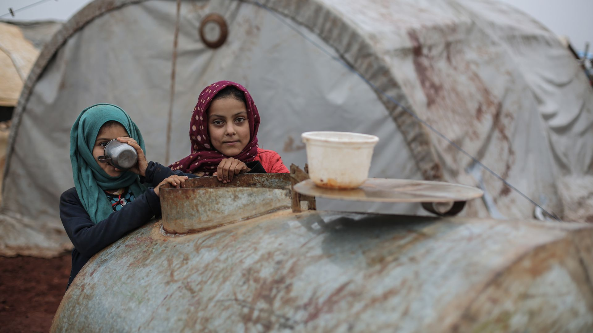 Displaced Syrian girls lean on a cistern during rainy weather at a camp for Syrian displaced people near the Syrian-Turkish border in the Northern countryside of Idlib.
