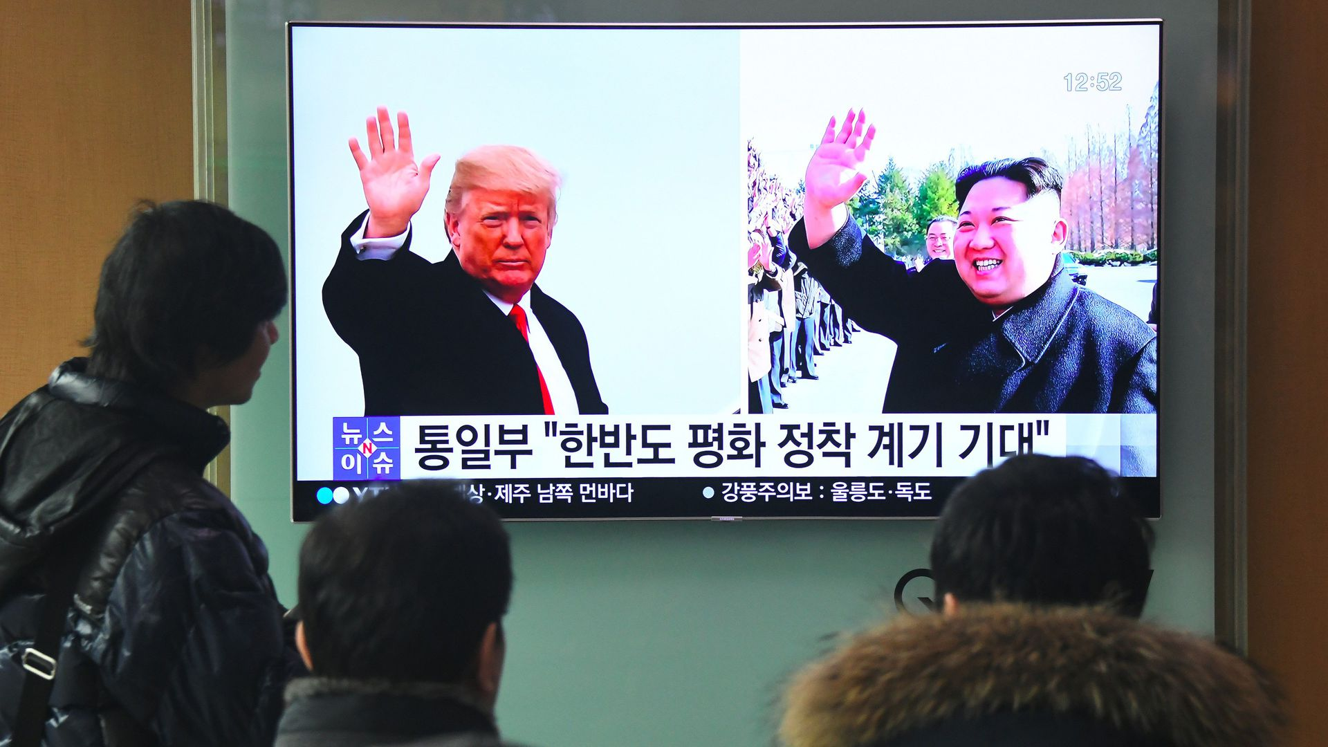 TV in Seoul train station showing Trump and Kim waving in separate photos