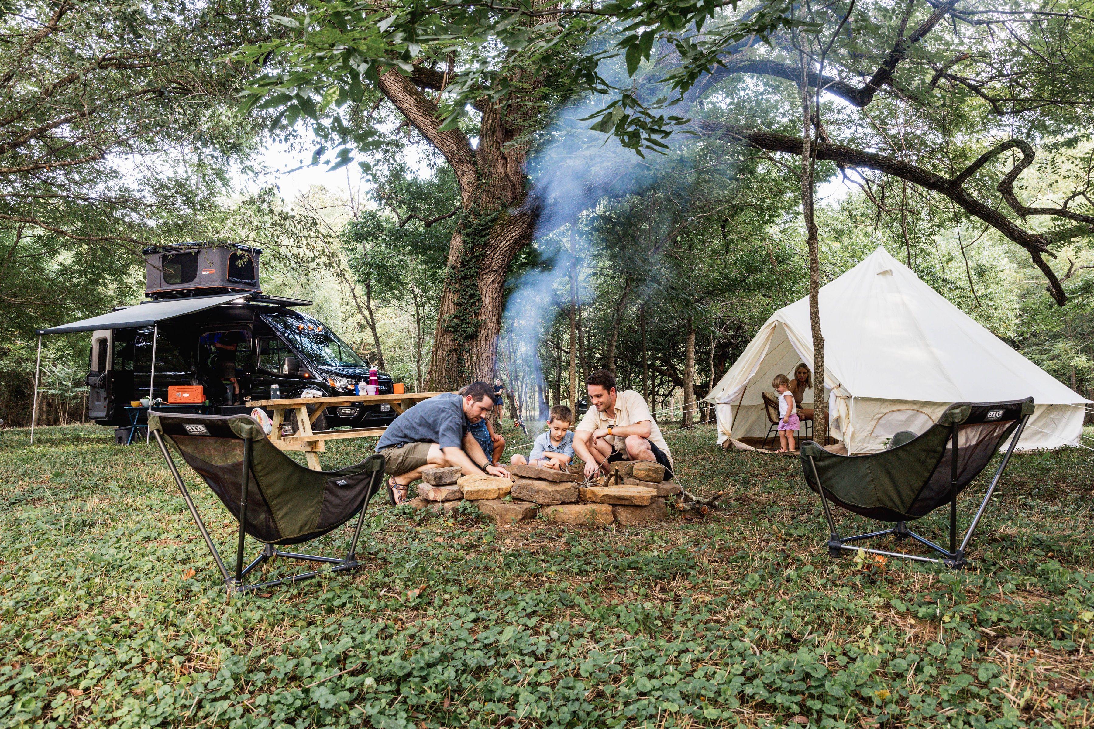 Photo of a family camping huddled near a campfire.