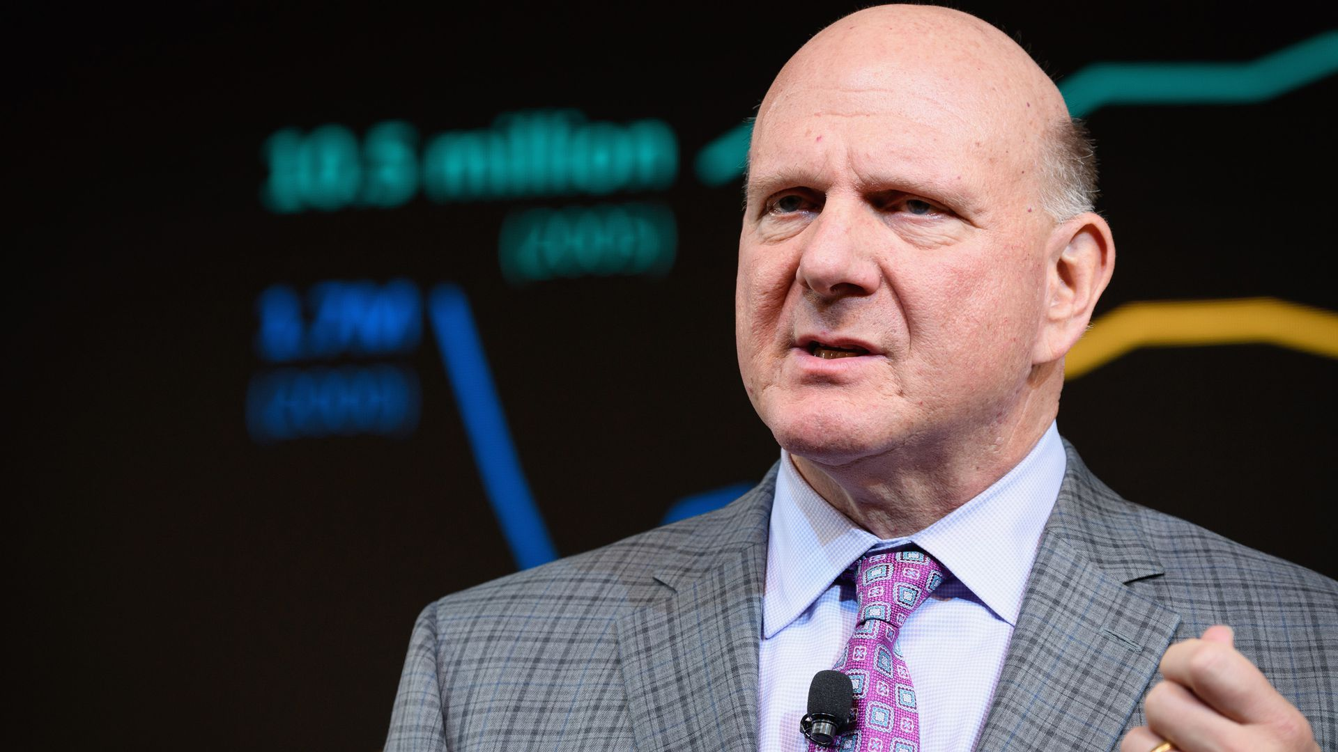 In this image, Steve Balmer speaks to an audience in a suit.